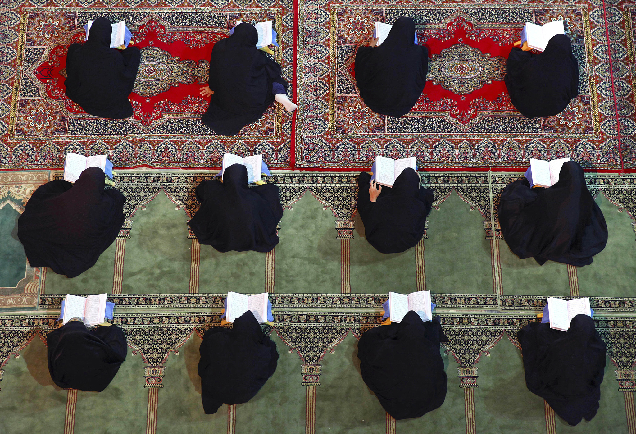 Iranian women recite verses of the Quran, Islam's holy book, during the Muslim holy fasting month of Ramadan at the shrine of Saint Mohammad Helal Ibn Ali in the city of Aran and Bidgol, some 140 miles (225 kilometers) south of the capital Tehran, Iran, Friday, July 11, 2014. Ramadan is a Muslim holy month of fasting during which Muslims abstain from food, drink and other pleasures from sunrise to sunset. For believers, Ramadan is meant to be a time of reflection and worship, remembering the hardships of others and being charitable. (AP Photo/Vahid Salemi)