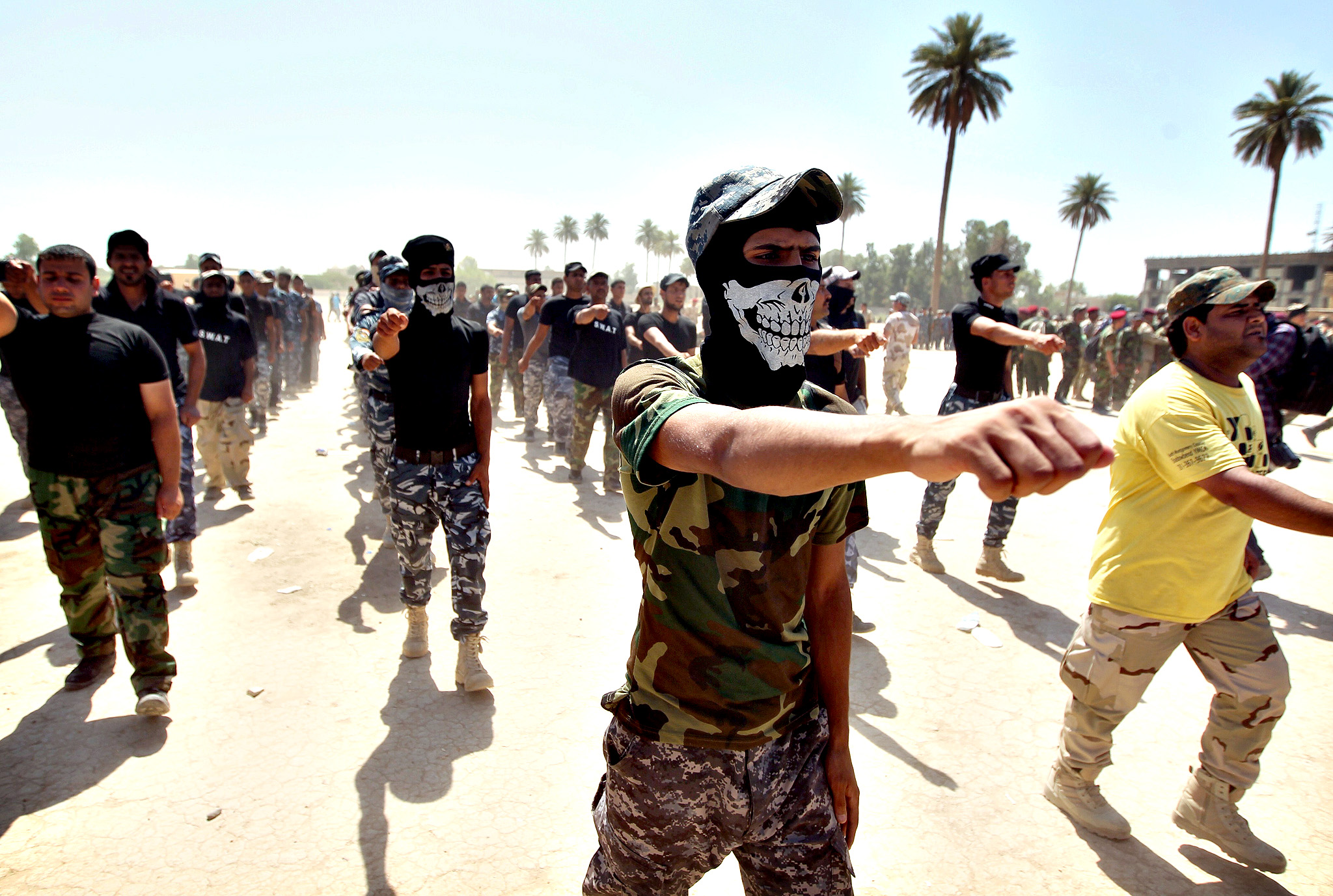 Shiite volunteers from the Iraqi Ketaeb (brigade) Hezbollah, march as they join the Iraqi army to fight against Jihadist militants of the Islamic State (IS), formerly known as the Islamic State in Iraq and the Levant (ISIL), on July 9, 2014, in Baghdad.. Iraq's government once battled entrenched Shiite militiamen but is now making common cause with them against a jihadist-led onslaught that Baghdad's forces are struggling to contain on their own.