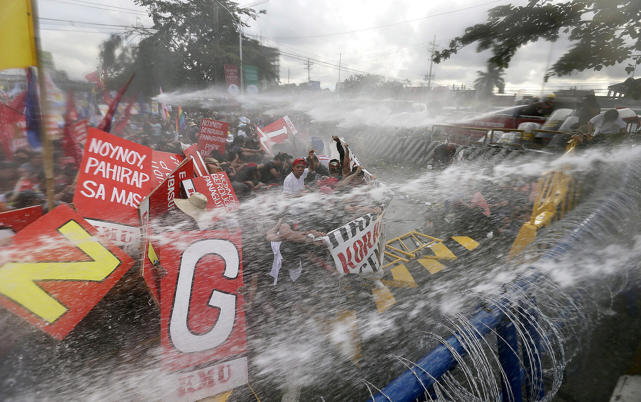 Protesters clash with riot police during President Aquino III's state of the nation address...epa04333631 Filipino anti-riot policemen use water cannon to disperse protestors attempting to reach the Philippine Congress in Quezon City, east of Manila, Philippines, 28 July 2014, during the state of the nation address (SONA) by Philippine president Benigno Aquino III. Thousands of protesters took to the streets in the Philippine capital , police said, during    President Benigno Aquino's annual state of the nation address.Police blocked off a main road leading to the House of Representatives compound in the Manila suburban city of Quezon, forcing the demonstrators to gather about three kilometres away. They brought an effigy of Aquino as a thief, accusing him of reneging on a vow to fight corruption by implementing an economic stimulus programme that allows for the discretionary distribution of state funds. The more than 3-billion-dollar programme was ruled unconstitutional by the Supreme Court, but Aquino's government appealed that decision.  EPA/DENNIS M. SABANGAN