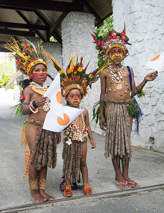 Local children wave Japanese flags as Japan's Prime Minister Shinzo Abe arrives in the Papua New Guinea capital of  Port Moresby on July 10, 2014.  Abe is visiting New Zealand, Australia and Papua New Guinea to hold talks with officials on biliateral and international issues