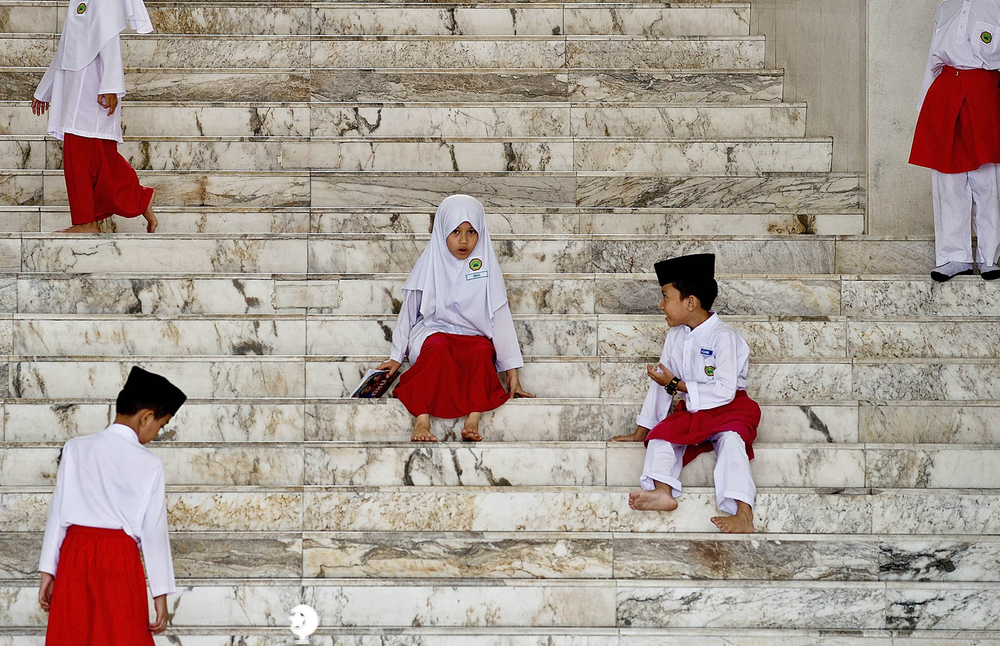 TOPSHOTS Young Malaysian Muslim children...TOPSHOTS Young Malaysian Muslim children play on the steps of a mosque after attending their classes during the Islamic month of Ramadan in Kuala Lumpur on July 2, 2014.  Across the Muslim world, the faithful fast from dawn to dusk, and abstain from eating, drinking, smoking and having sex during that time as they strive to be more pious and charitable.   AFP PHOTO / MANAN VATSYAYANAMANAN VATSYAYANA/AFP/Getty Images