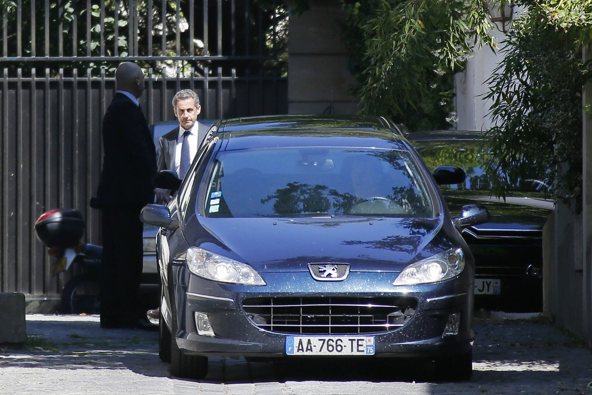 Former French President Nicolas Sarkozy leaves his residence in Paris...Former French President Nicolas Sarkozy (R) leaves his residence in Paris, July 2, 2014. Former French President Nicolas Sarkozy was placed under formal investigation on Wednesday on suspicions he tried to use his influence to thwart an investigation of his 2007 election campaign, the prosecutor's office said.   REUTERS/Gonzalo Fuentes (FRANCE - Tags: POLITICS CRIME LAW)    ATTENTION EDITORS FRENCH LAW REQUIRES THAT CAR REGISTRATION PLATES ARE MASKED IN PUBLICATIONS WITHIN FRANCE