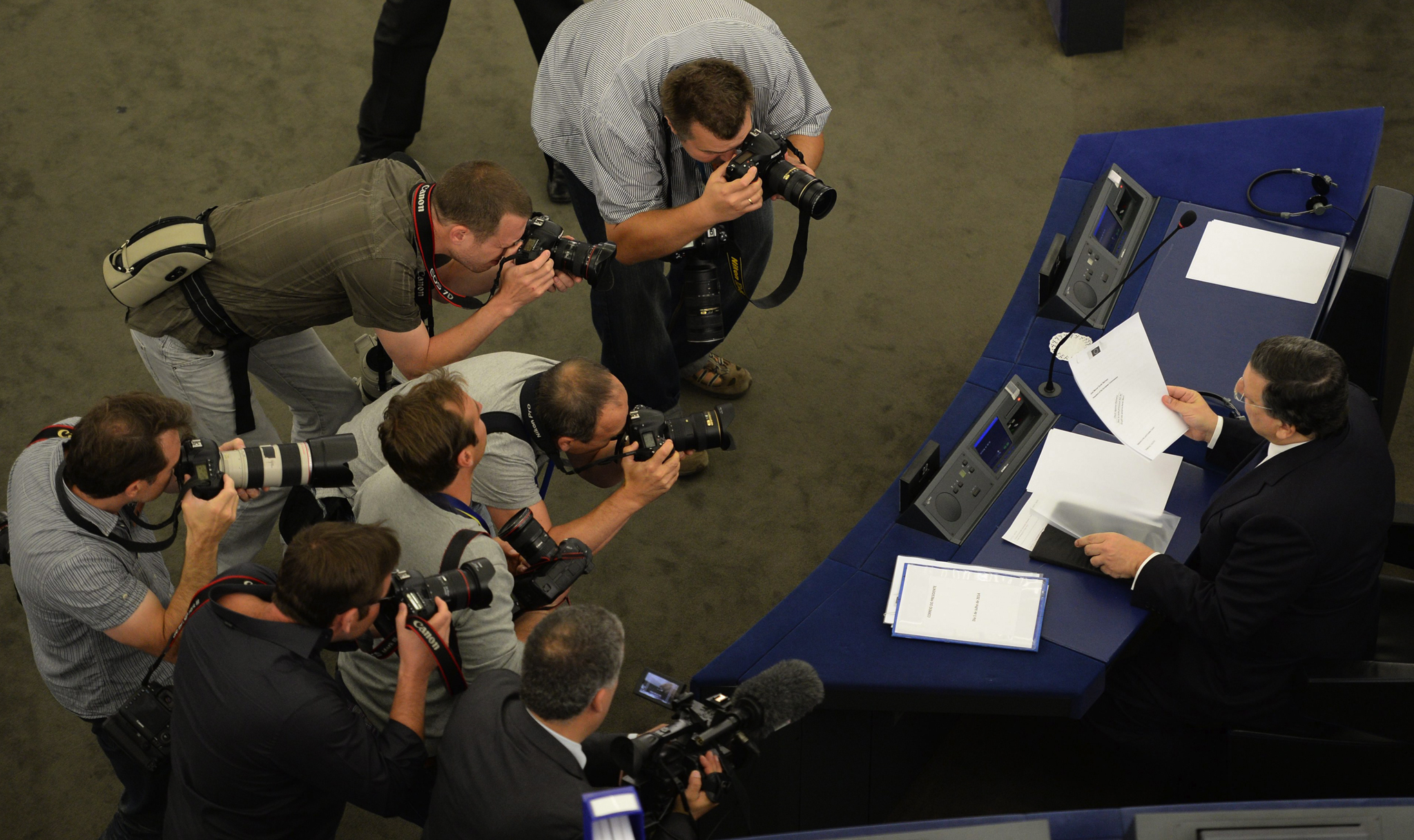 Outgoing European Commission President Jose Manuel Barroso is watched by photographers as he reads in his papers on the second day of plenary session at the European Parliament in Strasbourg,