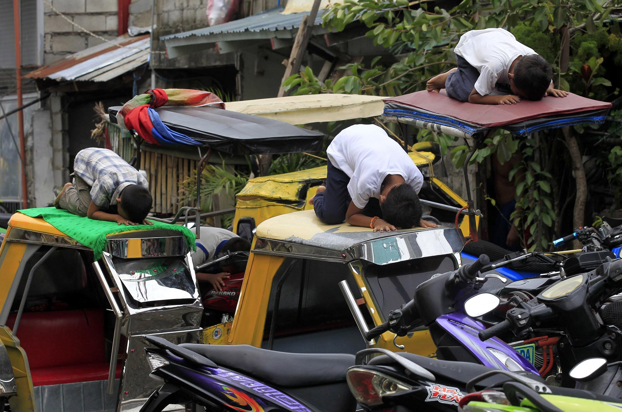 Muslim youths pray atop motorcycle taxis during the fasting month of Ramadan in front of Al-Satie Mosque in Baseco, Tondo city, metro Manila