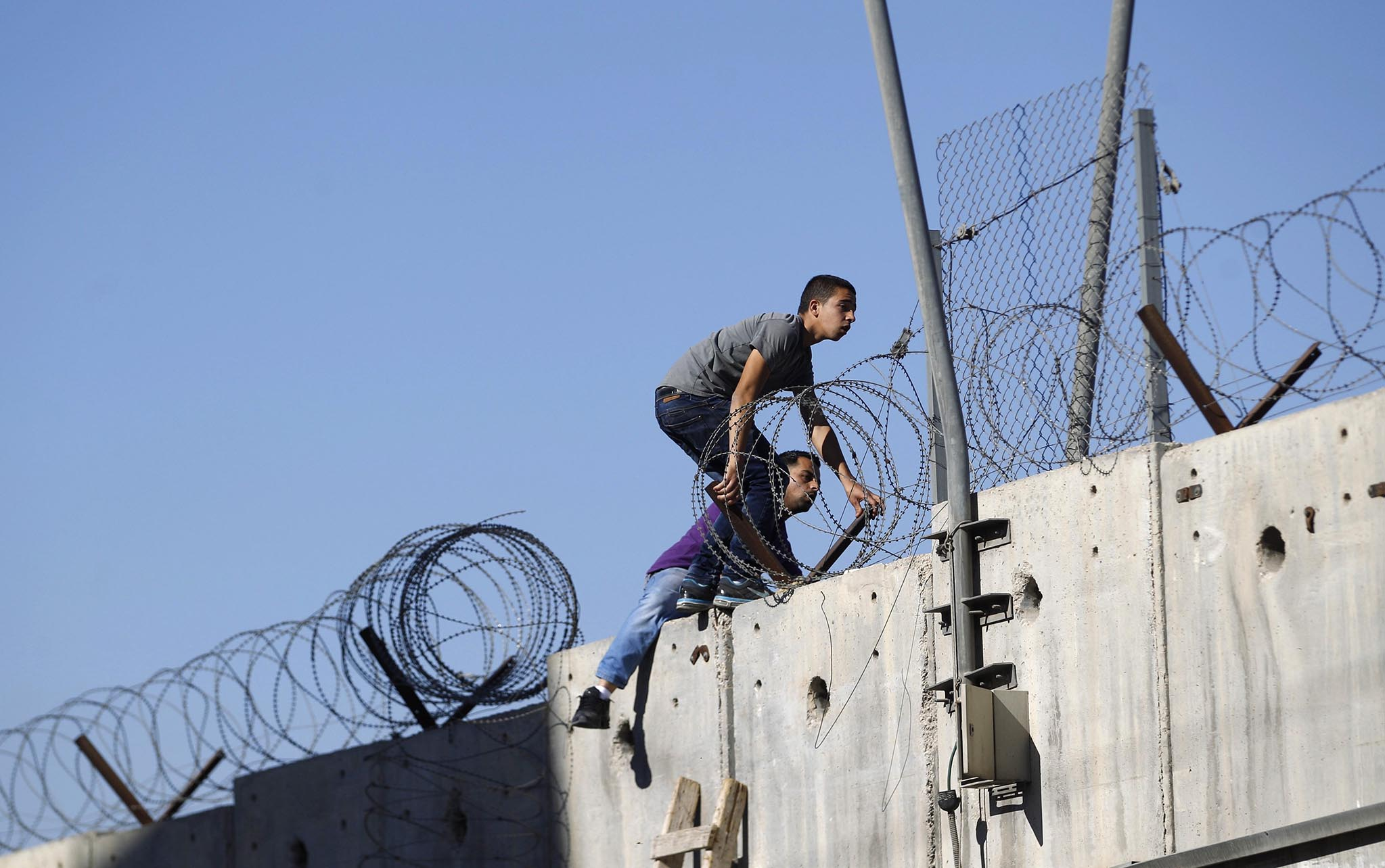 om the West Bank due to an age limit, climb over a section of the controversial Israeli barrier, in the village of Al-Ram