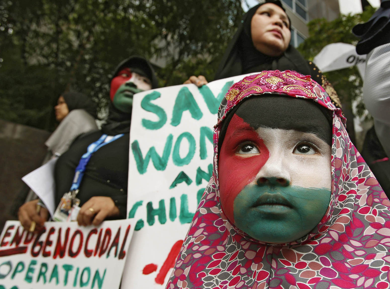 A Filipino Muslim girl, with the colours of the Palestinian flag painted on her face, stands near her mother during a rally held by the Anak Mindanao in Taguig