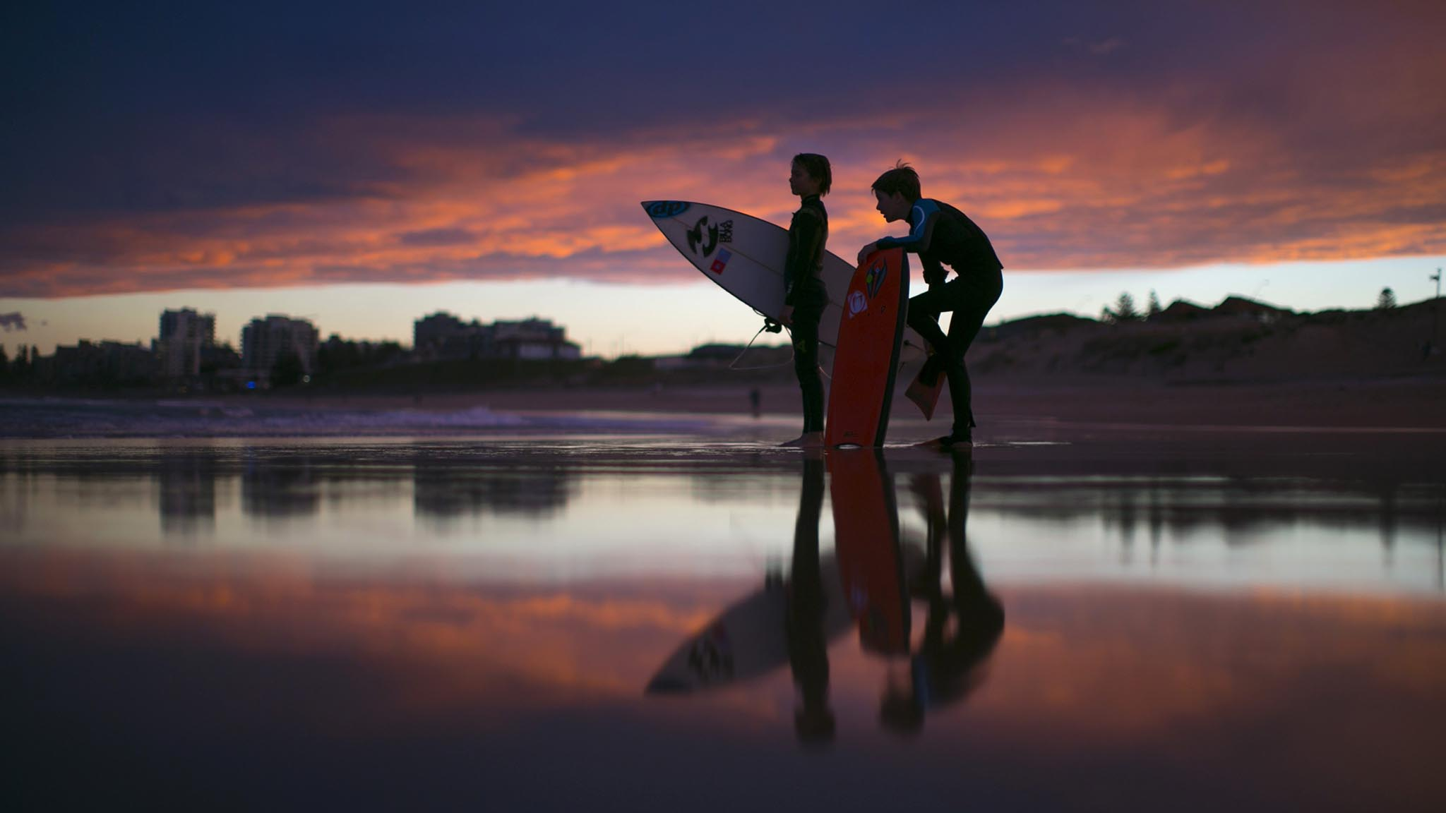 Young surfers, nicknamed 'grommets' in local surfing parlance, wait for their friends to finish a post-sunset session on the waves off Wanda Beach in Sydney