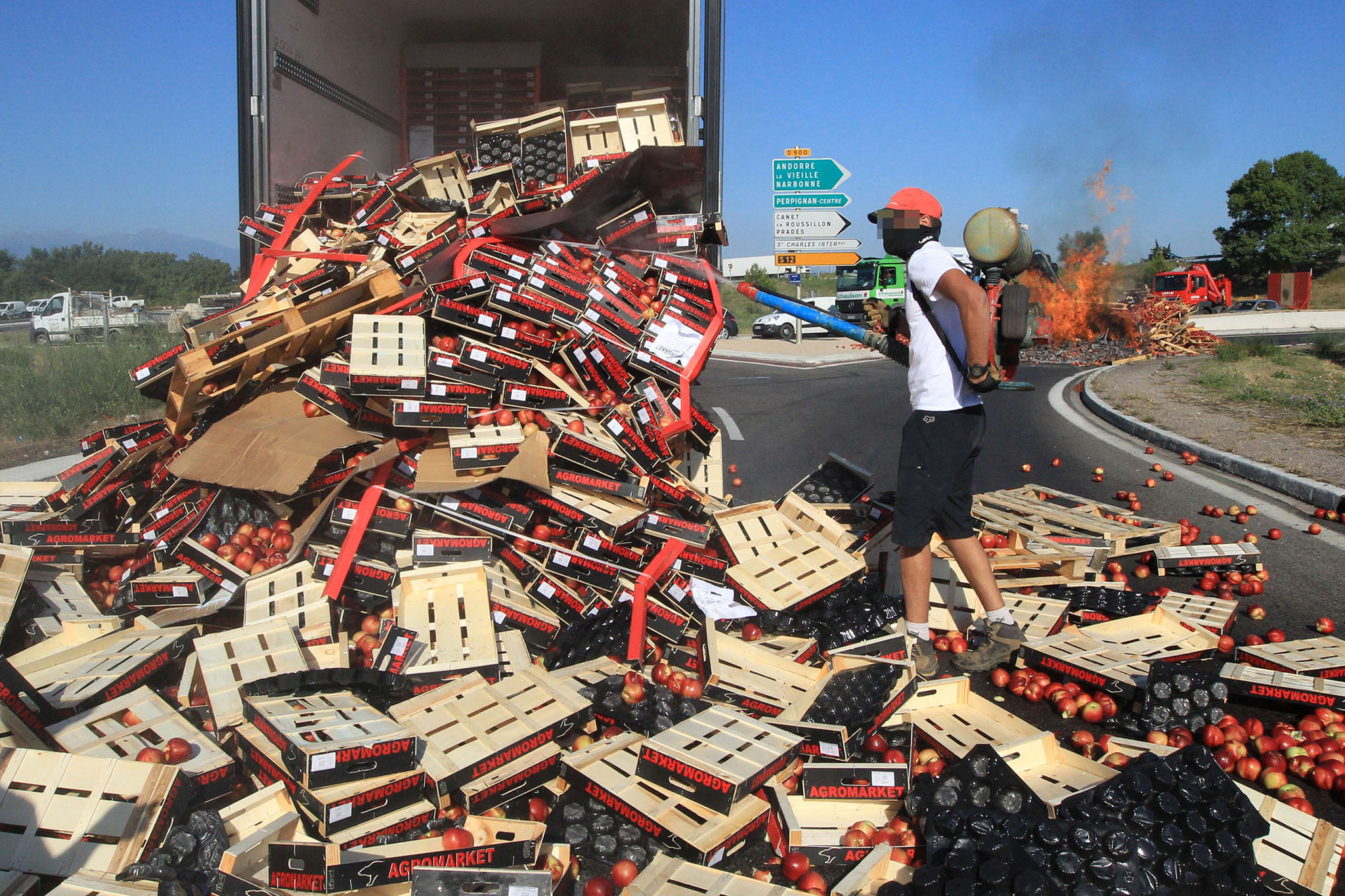 A protester neutralizes with fuel the freight of peaches from a Spanish truck after protesters discharge peaches and set fire (at background) to the crates of fruits during a demonstration at a toll bridge on the A9 motorway near Perpignan, southern France, on July 17, 2014 to protest against fruit importation low prices. AFP/ PHOTO RAYMOND ROIGRAYMOND ROIG/AFP/Getty Images