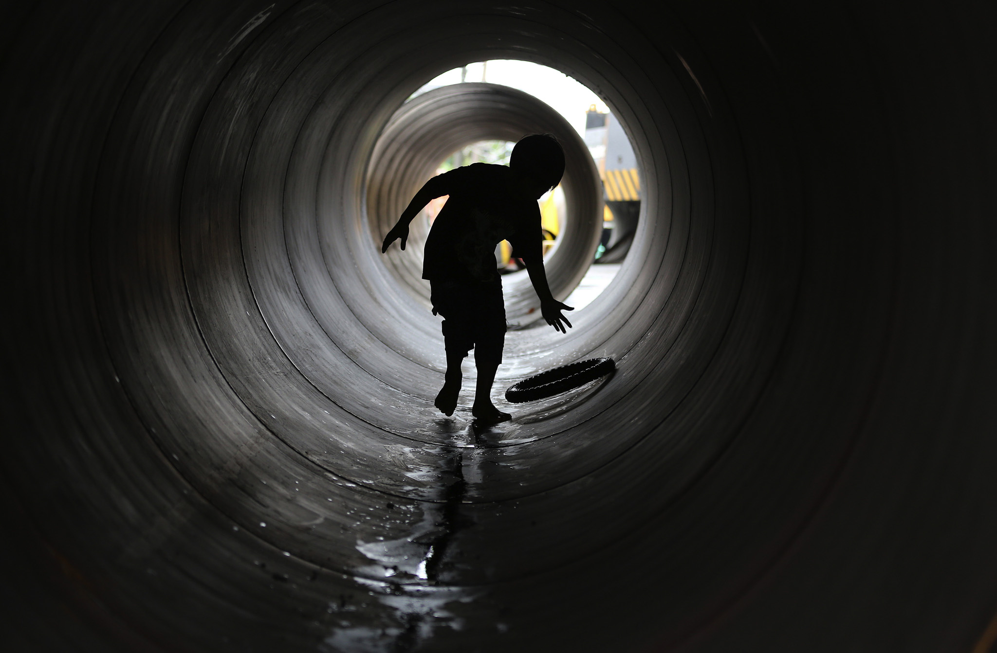 A Filipino boy plays inside a large metal tube that will be used to repair an old bridge in suburban Malabon, north of Manila, Philippines.