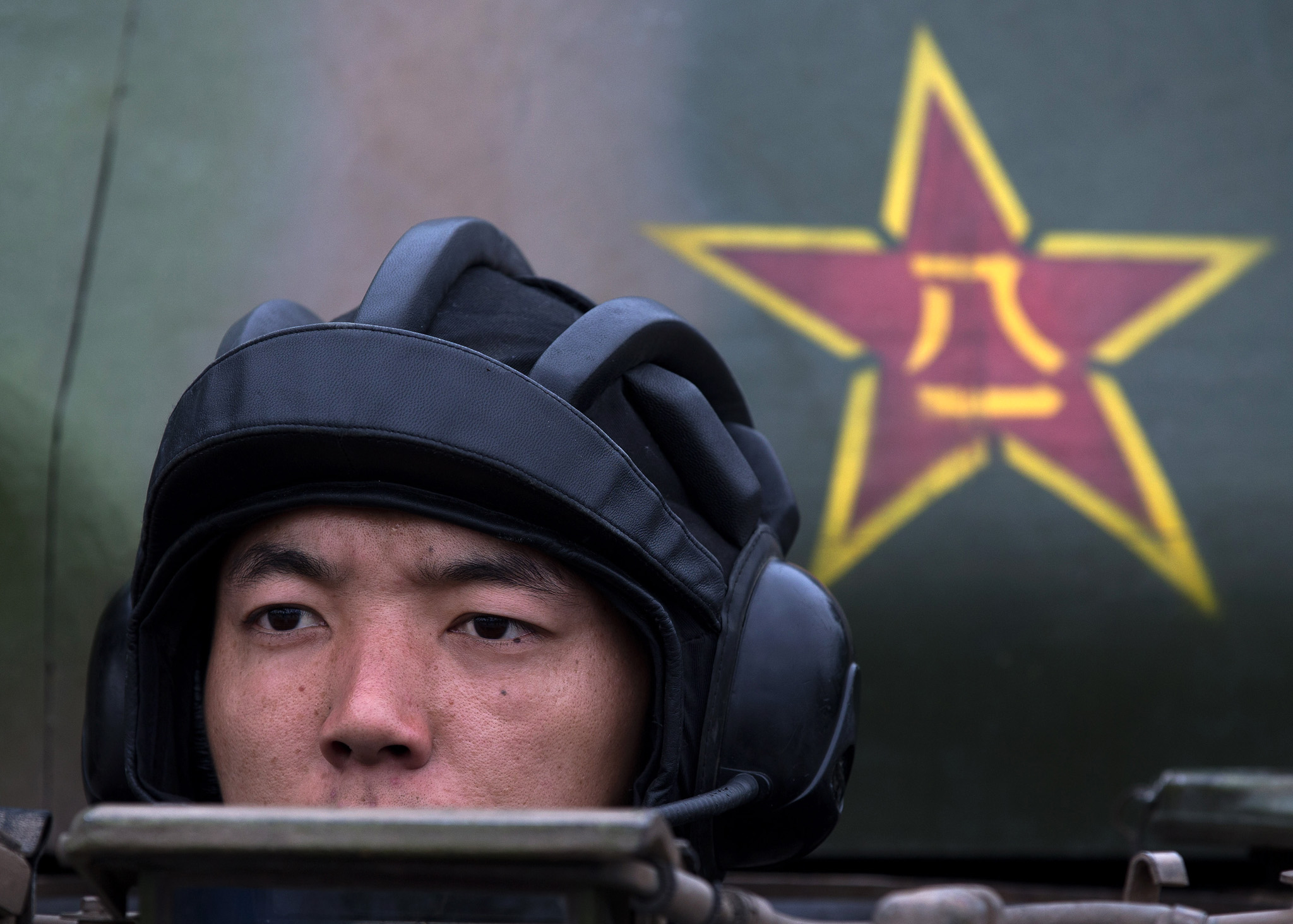 A Chinese People's Liberation Army cadet sits in a Main Battle Tank during a demonstration at the PLA's Armoured Forces Engineering Academy Base, in the outskirt of Beijing.