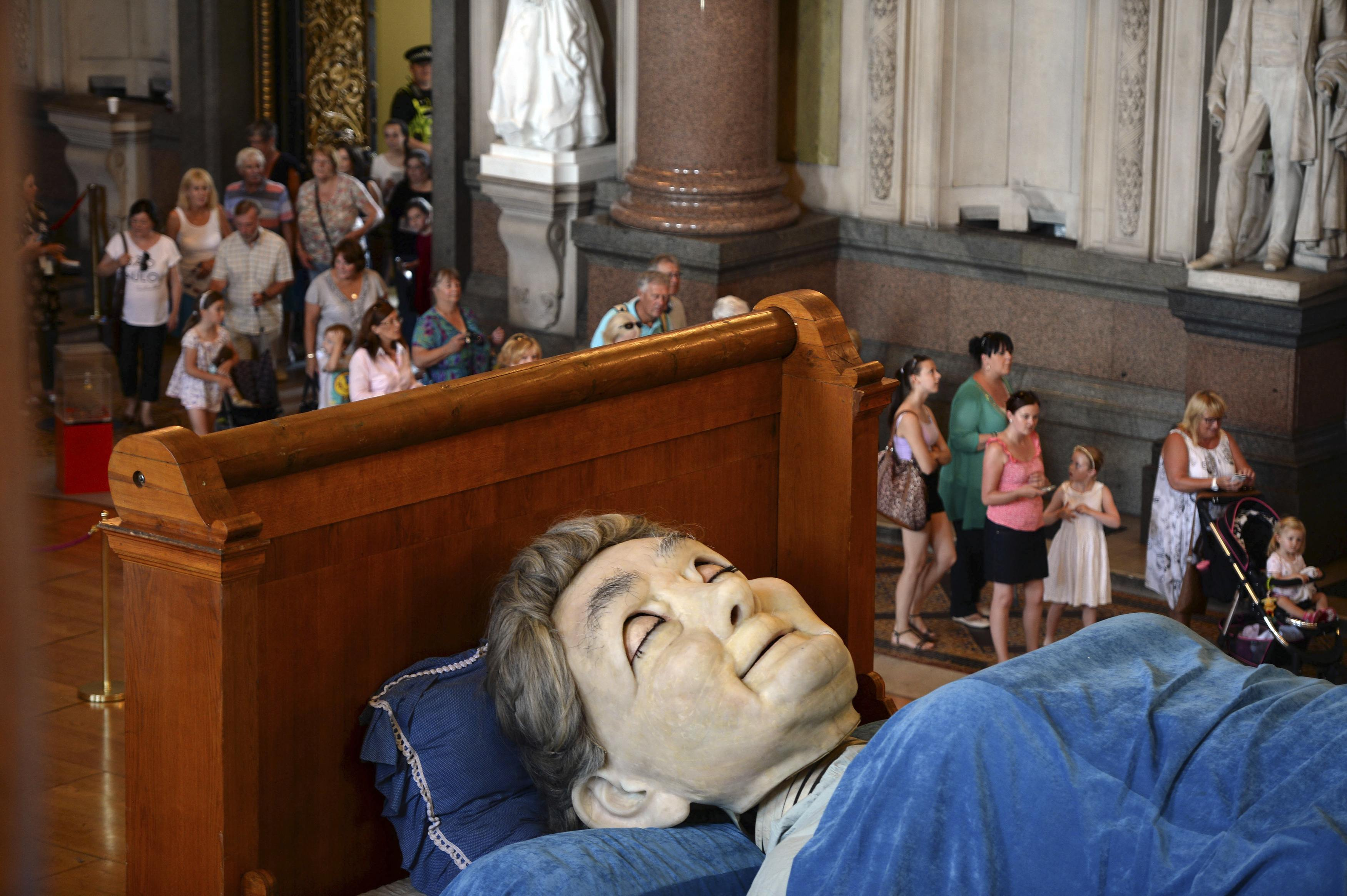 Visitors look at a giant puppet of a grandmother sleeping on a bed inside St George's Hall in Liverpool