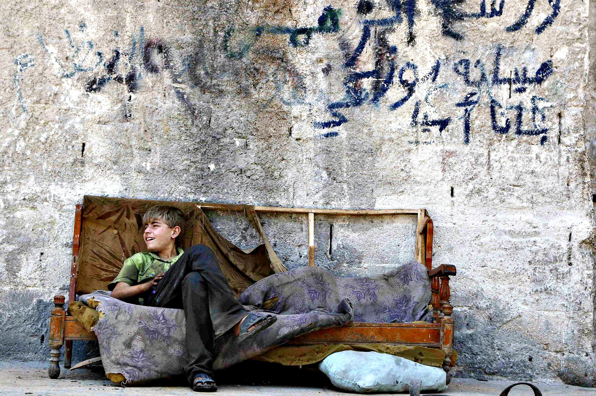 A boy sits on a sofa along a street in the Al-Fardous neighbourhood of Aleppo July 15, 2014.