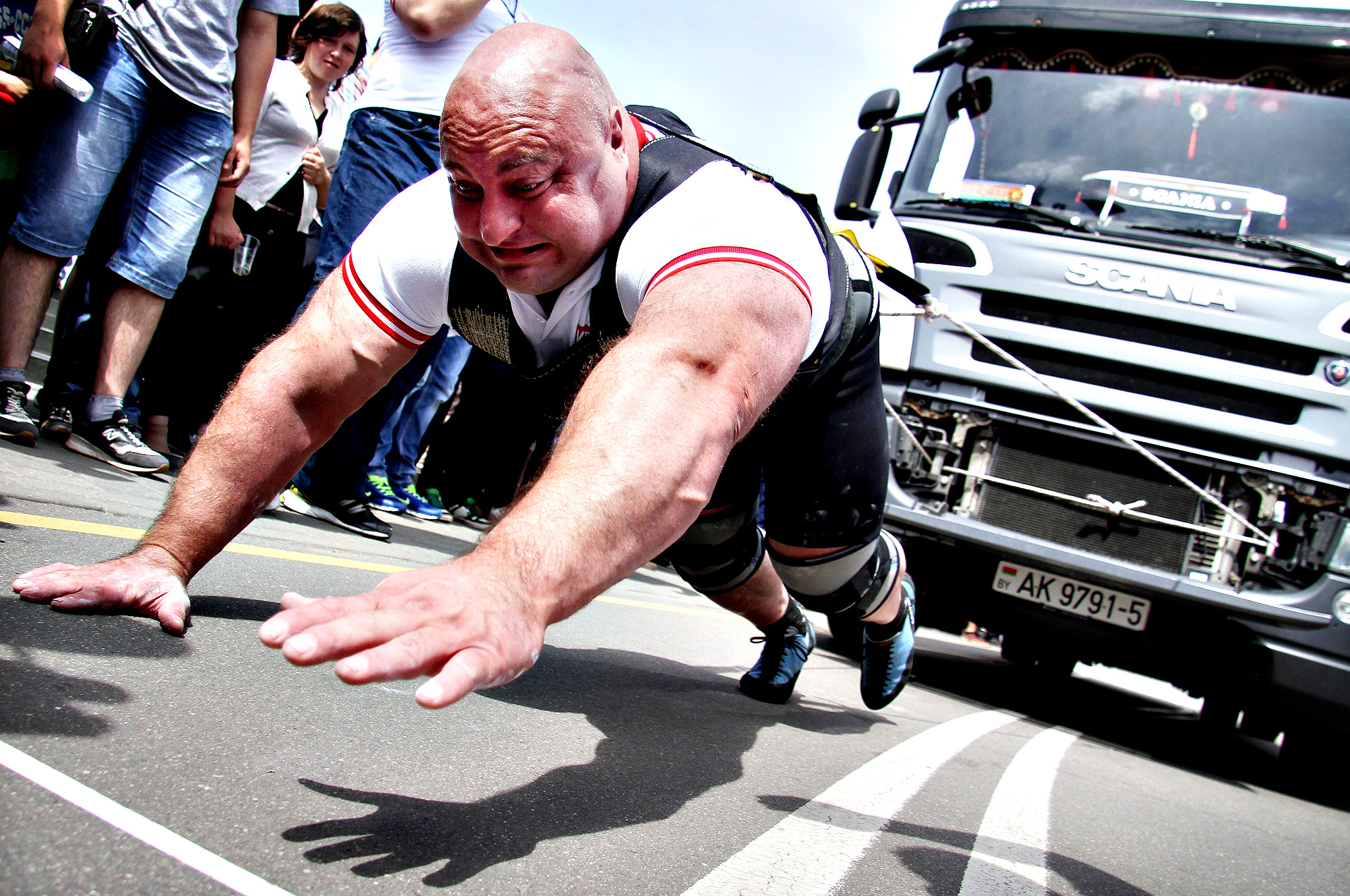 An athlete pulls a 15-tonne truck during a Truck-Pull event marking the upcoming Independence Day in the Belarus capital Minsk,  on July 3, 2014.  The former Soviet nation celebrates its Independence Day on July 3 in memory of the end of Belarus occupation by Nazi Germany troops during the Red Army main summer offensive in 1944.