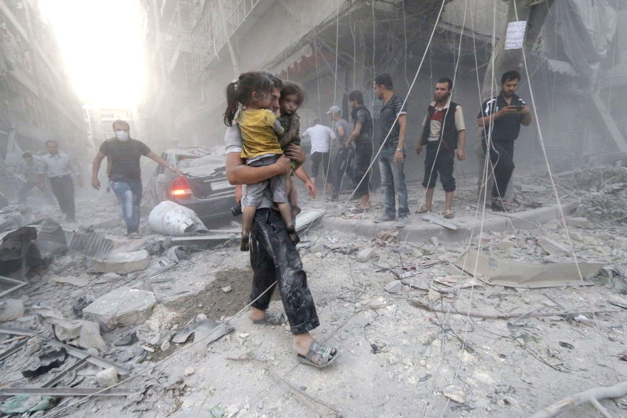 A Syrian man carries two girls covered with dust