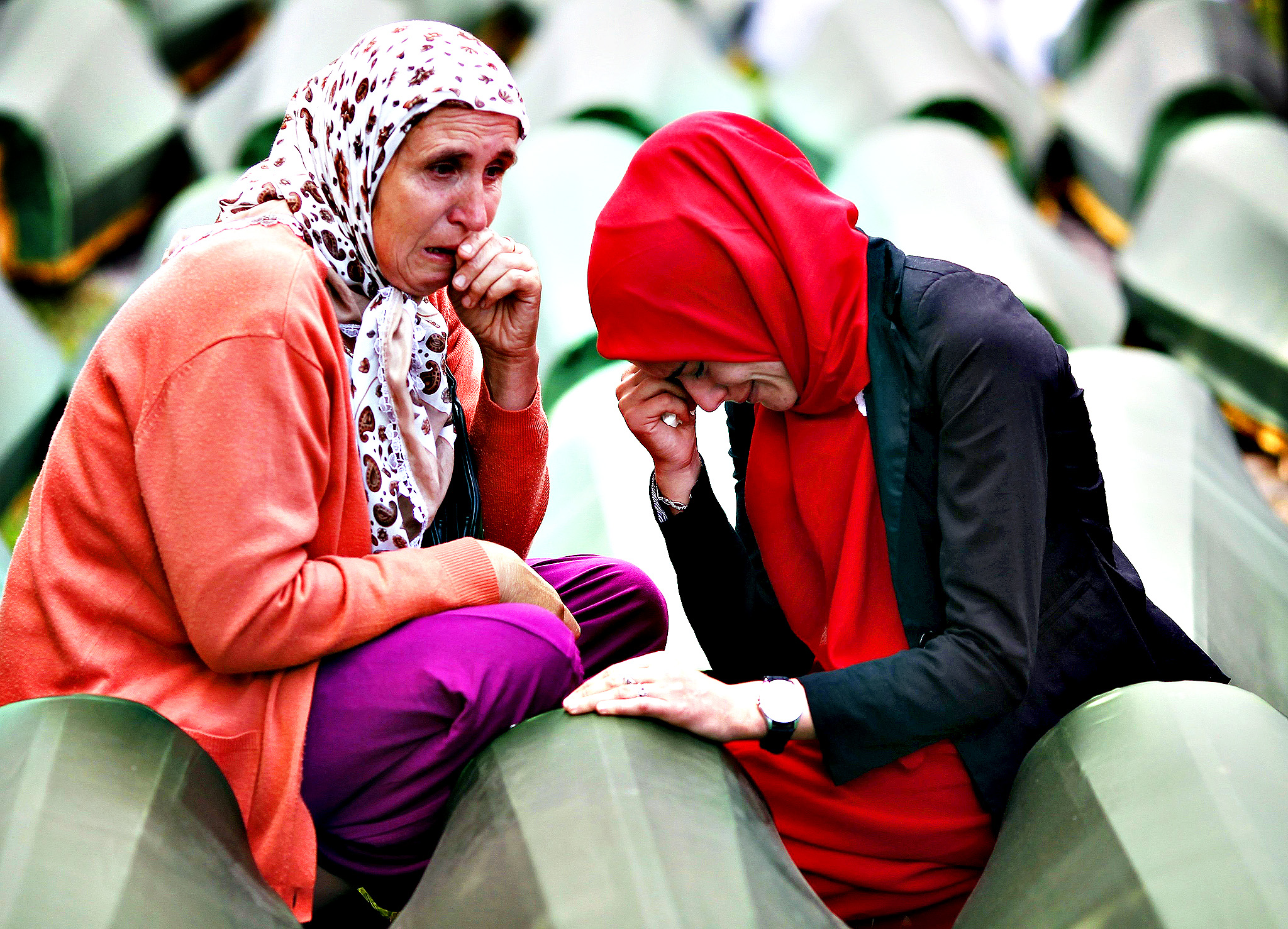 Bosnian Muslim women cry near the coffin of a relative, one of the 175 coffins of newly identified victims from the 1995 Srebrenica massacre, in Potocari Memorial Center, near Srebrenica...Bosnian Muslim women cry near the coffin of a relative, one of the 175 coffins of newly identified victims from the 1995 Srebrenica massacre, in Potocari Memorial Center, near Srebrenica, July 11, 2014. Family members, foreign dignitaries and guests are expected to attend a ceremony in Srebrenica on Friday marking the 19th anniversary of the massacre in which Bosnian Serb forces commanded by military commander Ratko Mladic killed up to 8,000 Muslim men and boys. The remains of the 175 identified victims will be buried at a memorial cemetery during the ceremony, their bodies found in some 60 mass graves around the town.