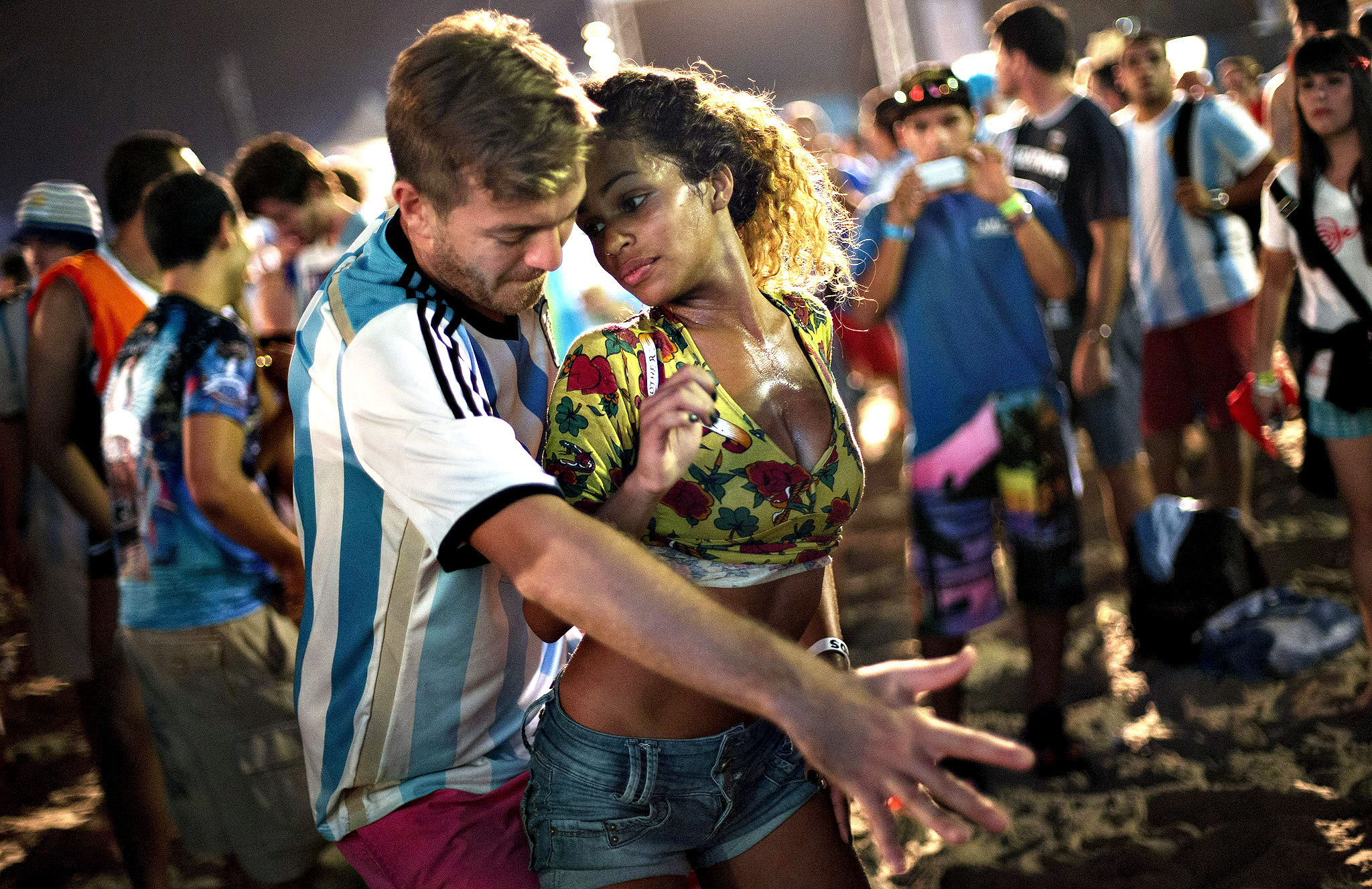 A woman from Brazil and a man from Argentina dance samba at the World Cup Fan Fest 2014, on Copacabana beach, in Rio de Janeiro, Brazil, Wednesday, July 9, 2014. The flood of foreign football fans, the vast majority of them men, has been a boon for the single ladies of Brazil, where a demographic imbalance means women outnumber men by more than 4 million nationally.