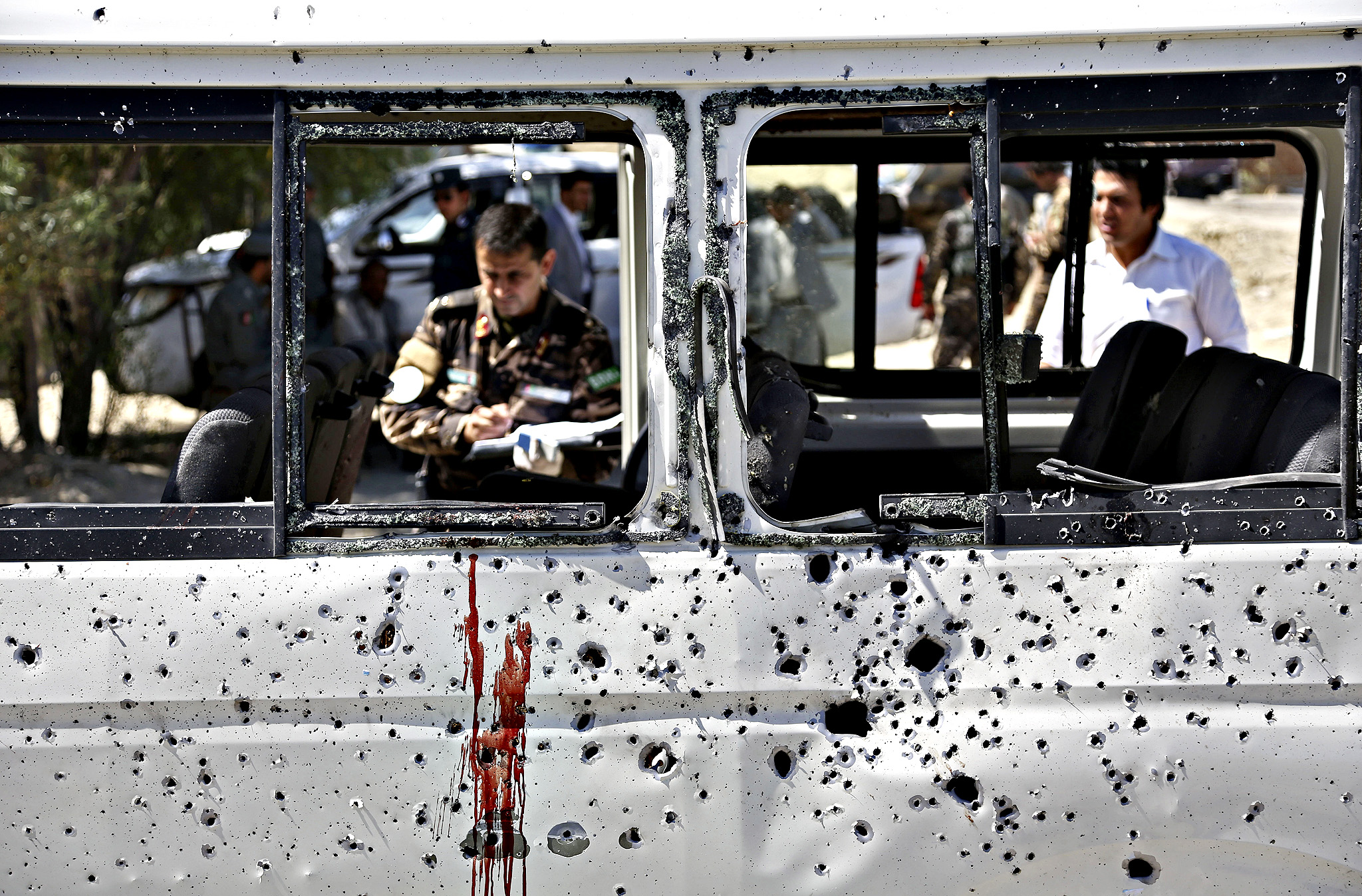 Afghan security personnel investigate a damaged minivan which was hit by a remote controlled bomb on the outskirts of Kabul, Afghanistan, Tuesday, July 15, 2014. Gul Agha Hashimi, the chief of criminal investigations with the Kabul police, said the explosion struck the minivan carrying seven staffers of the palace's media office on Tuesday morning. The blast killed two passengers and also wounded five people, including the driver.