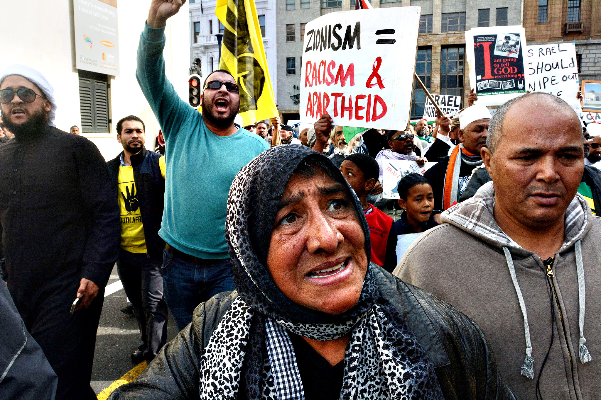 People hold placards and shout slogans while marching through Cape Town to protest Israel's military campaign in Gaza and show their support to the Palestinian people, on July 16, 2014. Israel urged 100,000 Gazans to flee their homes on July 16, but the warning was largely ignored despite an intensification of the military's nine-day campaign after Hamas snubbed a ceasefire effort.