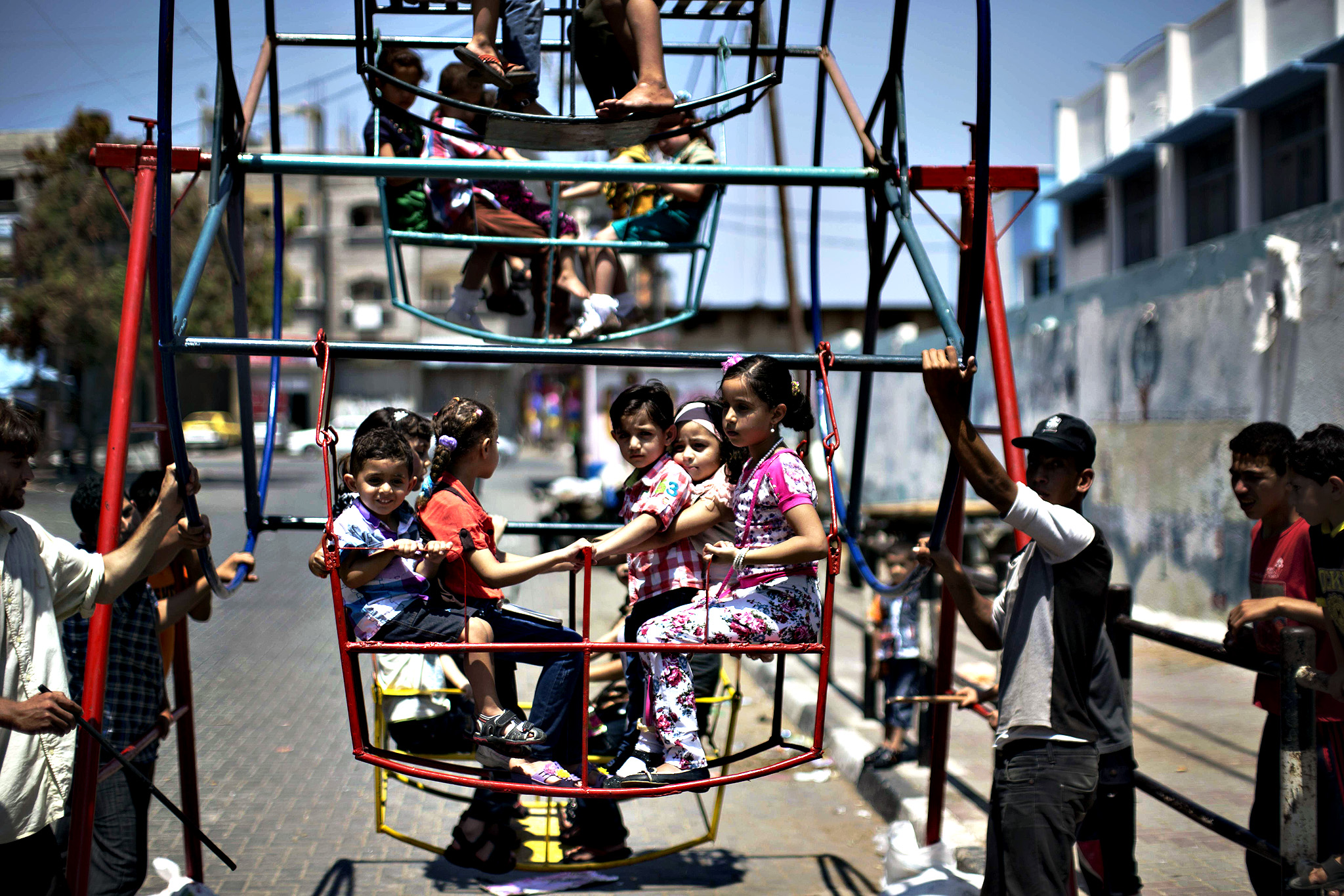 Palestinian children play on a mini ferris wheel outside an United Nations (UN) school in Jabalia in the northern Gaza strip, on July 28, 2014, on the beginning of the Muslim Eid festival ending the month-long fast of Ramadan. Israeli tank fire killed a four-year-old boy in the northern Gaza Strip, the first death since the two sides began observing an unofficial lull, Palestinian medics said.