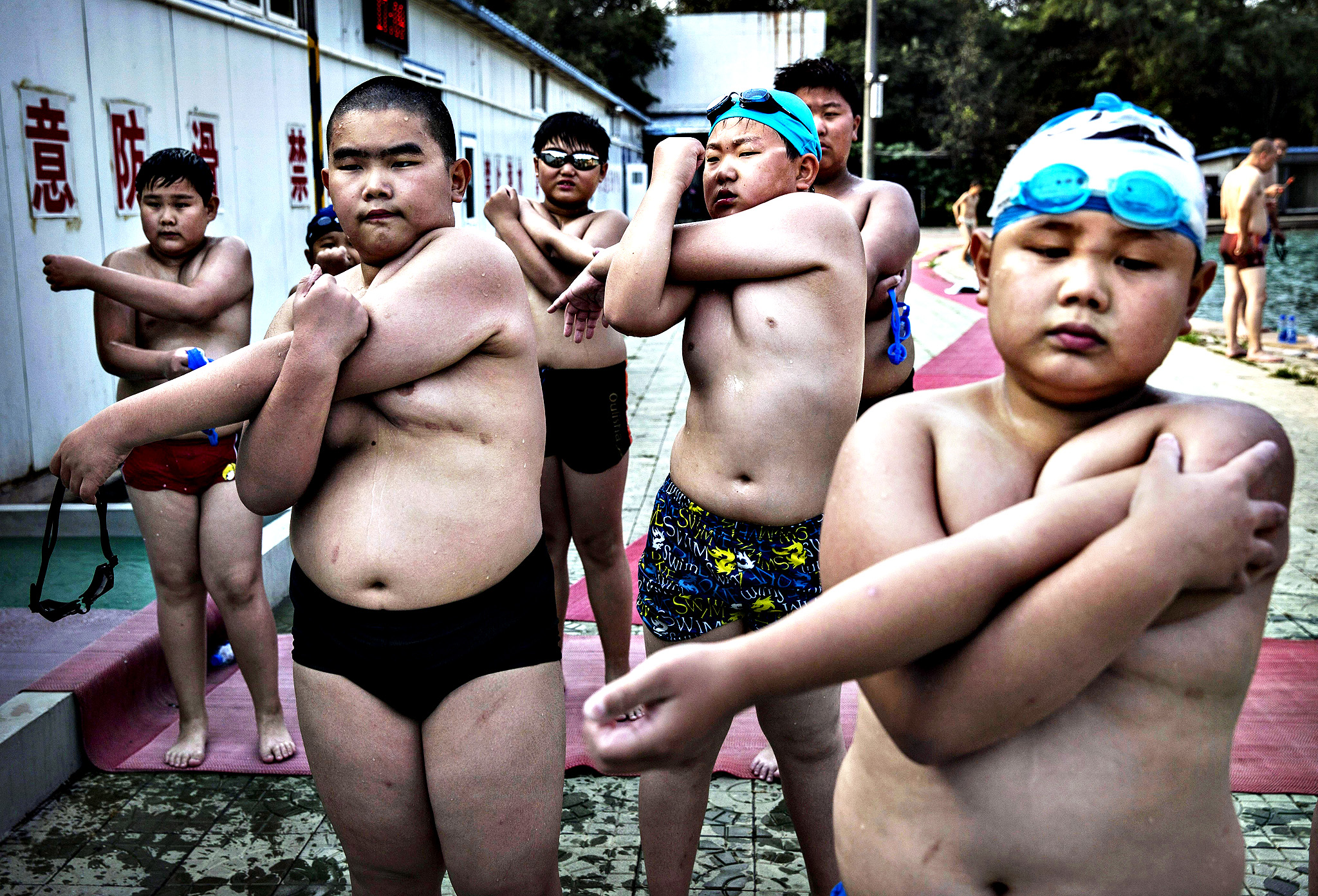 Overweight Chinese students stretch after swimming during training at a camp held for overweight children in Beijing, China