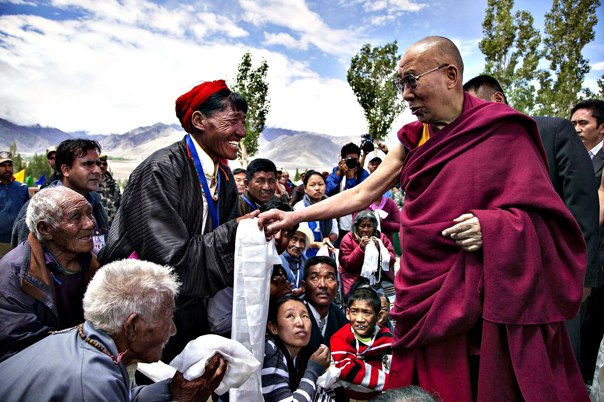 Tibetan spiritual leader the Dalai Lama, talks to a Buddhist devotee as he arrives at the Tibetan children's village school near Leh, India, Thursday, July 3, 2014. Buddhist devotees from across the globe are expected to arrive in this Himalayan region of Ladakh to attend the  Kalachakra  or Wheel of Time initiations by the Dalai Lama beginning Thursday.