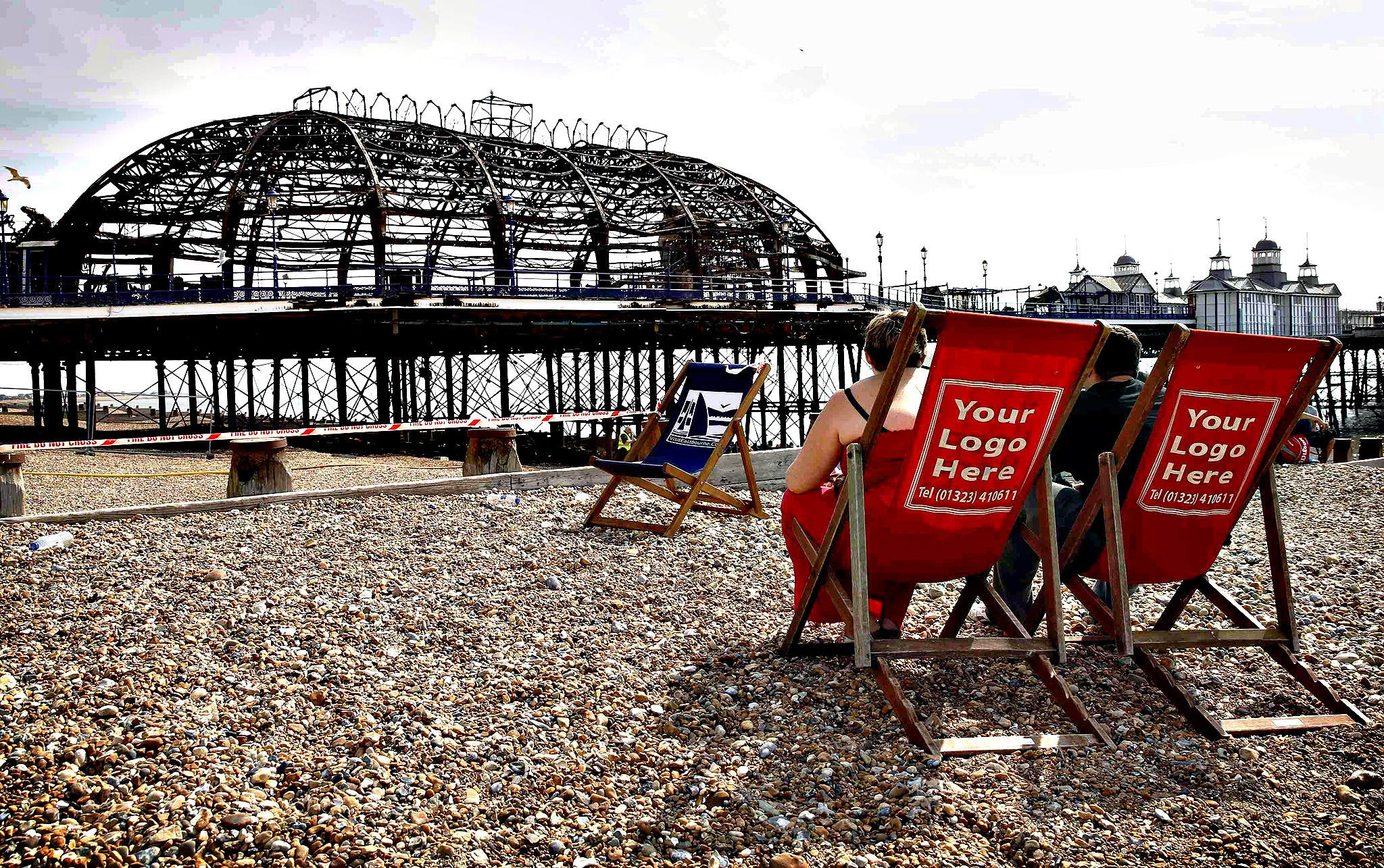 A couple sit in deckchairs on the beach next to the burnt remains of a section of Eastbourne pier, in Eastbourne, southern England July 31, 2014. A Victorian-era seaside pier at Eastbourne on Britain's south coast was badly damaged when fire broke out in an amusement arcade on Wednesday. Flames could be seen leaping from the roof of the two-storey structure as a large plume of smoke rose above the town. No injuries were reported.