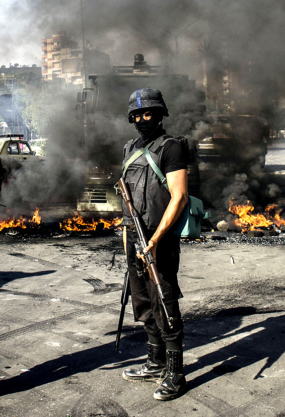 "An Egyptian riot policeman secures a street in front of burning tyres thrown by supporters of Muslim Brotherhood movement during their rally to mark the first anniversary of the military ouster of president Mohamed Morsi on July 3, 2014 in Cairo's Ain Shams district. Egyptian police swiftly quashed Islamist protests firing tear gas and arresting dozens of demonstrators, as the protests are seen as a test of the Islamists' strength, with the Muslim Brotherhood-led Anti Coup Alliance having issued an aggressive rallying cry demanding a ""day of anger"" to mark Morsi's overthrow."