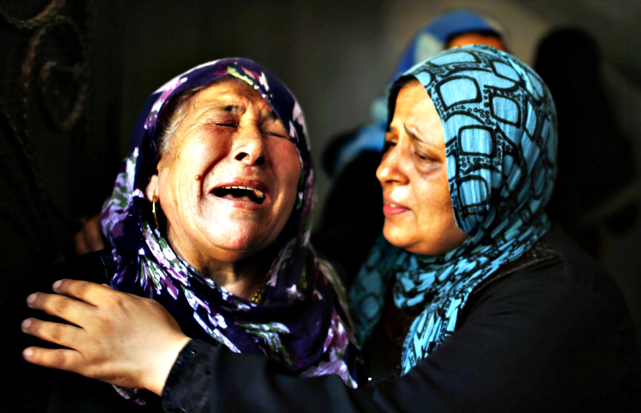 Palestinian relatives mourn during the funeral of members of Hamad family in the town of Beit Hanoun in the northern Gaza Strip July 9, 2014. Militants in Gaza fired more rockets at Tel Aviv on Wednesday, targeting Israel's heartland after Israeli attacks in the enclave that Palestinian officials said have killed at least 27 people. Israel assassinated a senior local leader of the Islamic Jihad militant group in the northern Gaza Strip early on Wednesday, neighbours and hospital officials said, and five others including family members were killed. An Israeli military spokeswoman said she had no initial details on the strike.The militant, Hafez Hamad, two brothers and his parents were killed when his house was bombed in an air strike in the town of Beit Hanoun in the northern Gaza Strip, Hamas media and Gaza interior ministry said. An unidentified woman in the house was also killed.