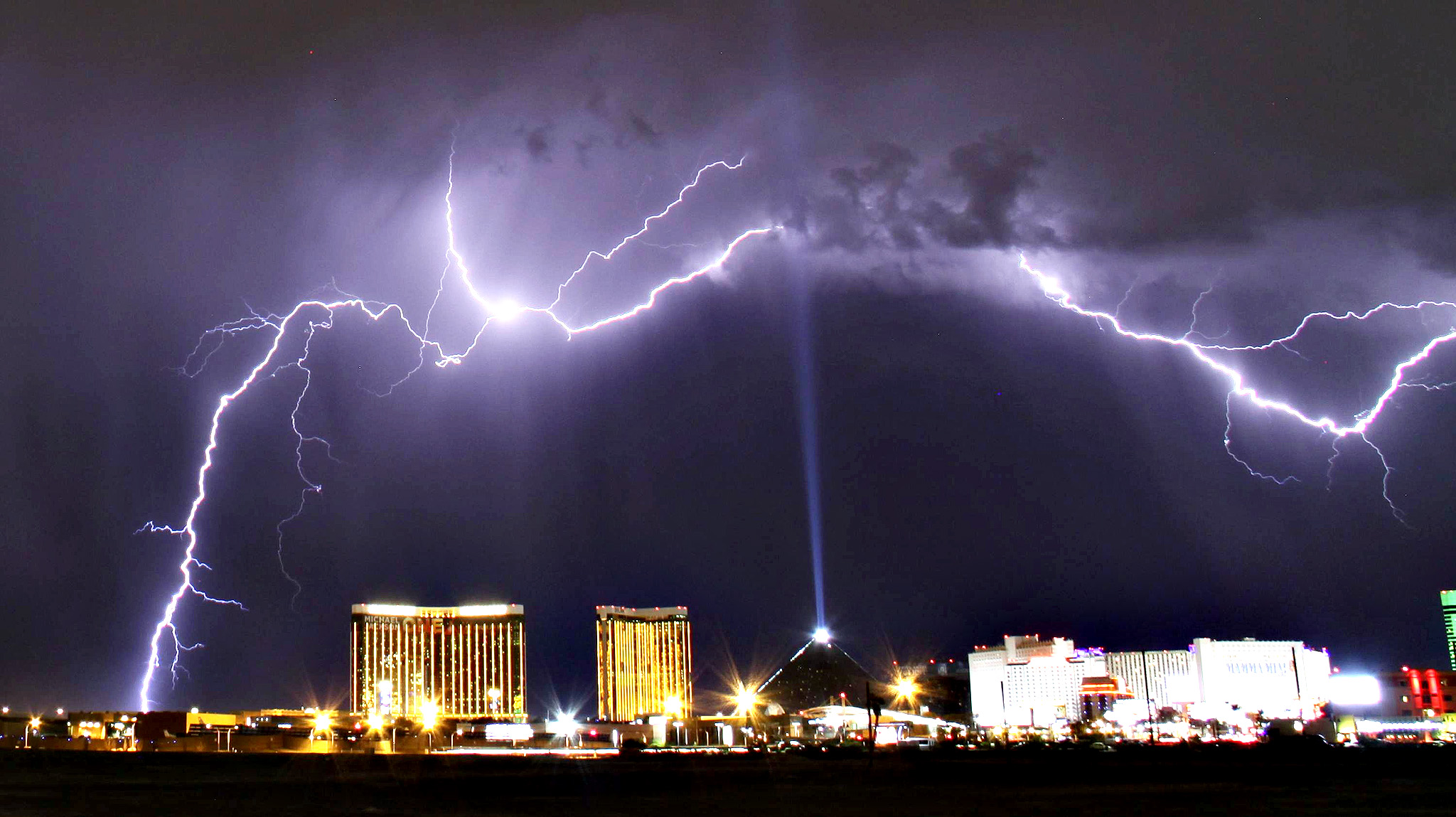 A monsoon lightning storm strikes over the Mandalay Bay Resorts and Casino and Luxor hotels in Las Vegas, Nevada late July 7, 2014. Monsoon storms are forecast for the the rest of the week in the Nevada and Arizona states.  The Luxor Sky Beam can be seen shining into the sky from the top of the hotel's pyramid structure.