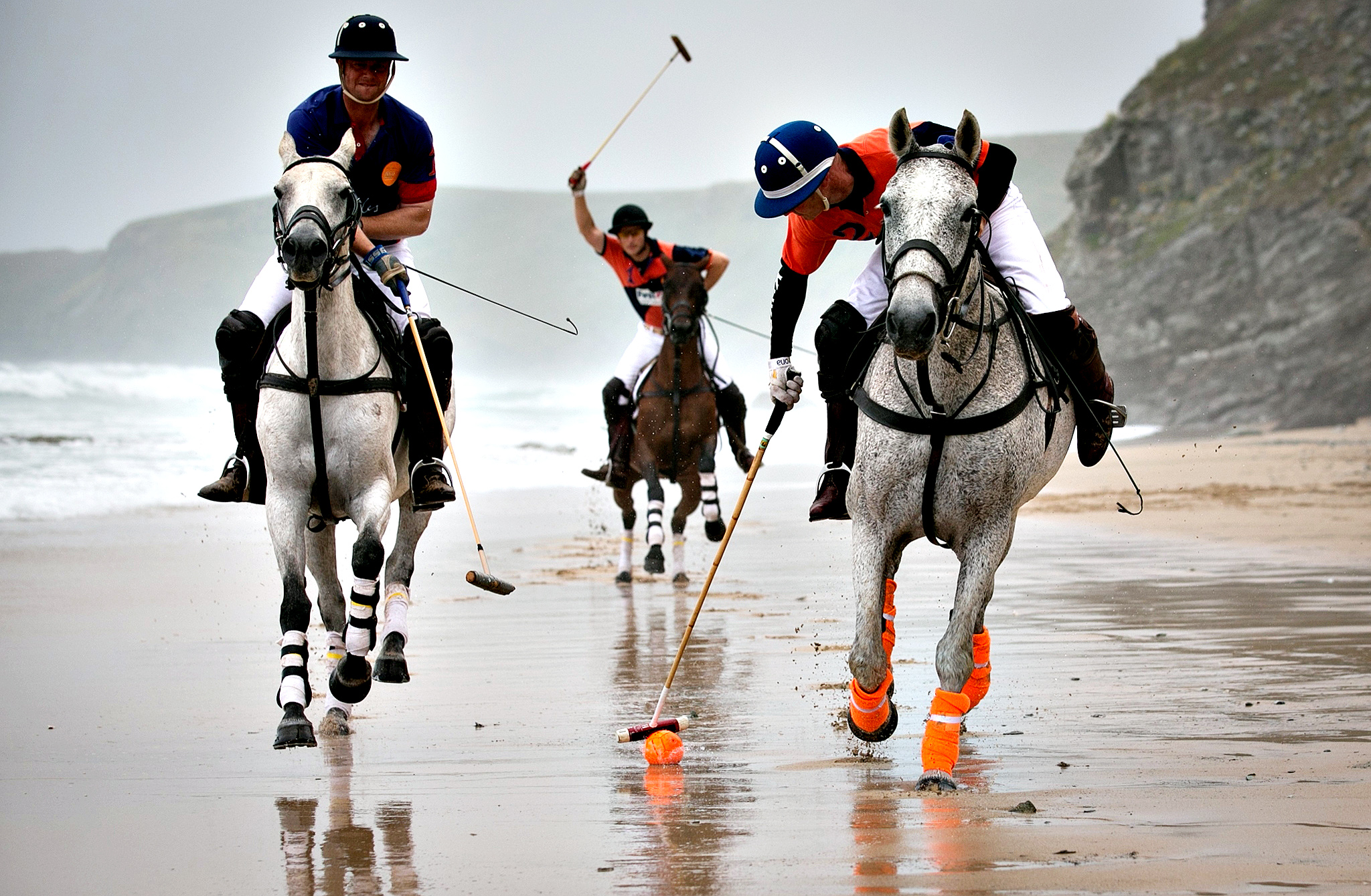 Polo players Andy Burgess (R) riding Tonka Rob Brockett riding Torda (L) and Ben Marshall (C) riding Shriva practice for the beach polo competition being held on the beach at Watergate Bay, near Newquay this weekend on July 4, 2014 in Cornwall, England. The players were practicing ahead of this weekend's 8th annual Veuve Clicquot Polo on the Beach at Watergate Bay, north Cornwall, which is taking place tomorrow and Sunday which attracts thousands of spectators to the beach and features some of England's top international players competing in a series of matches.