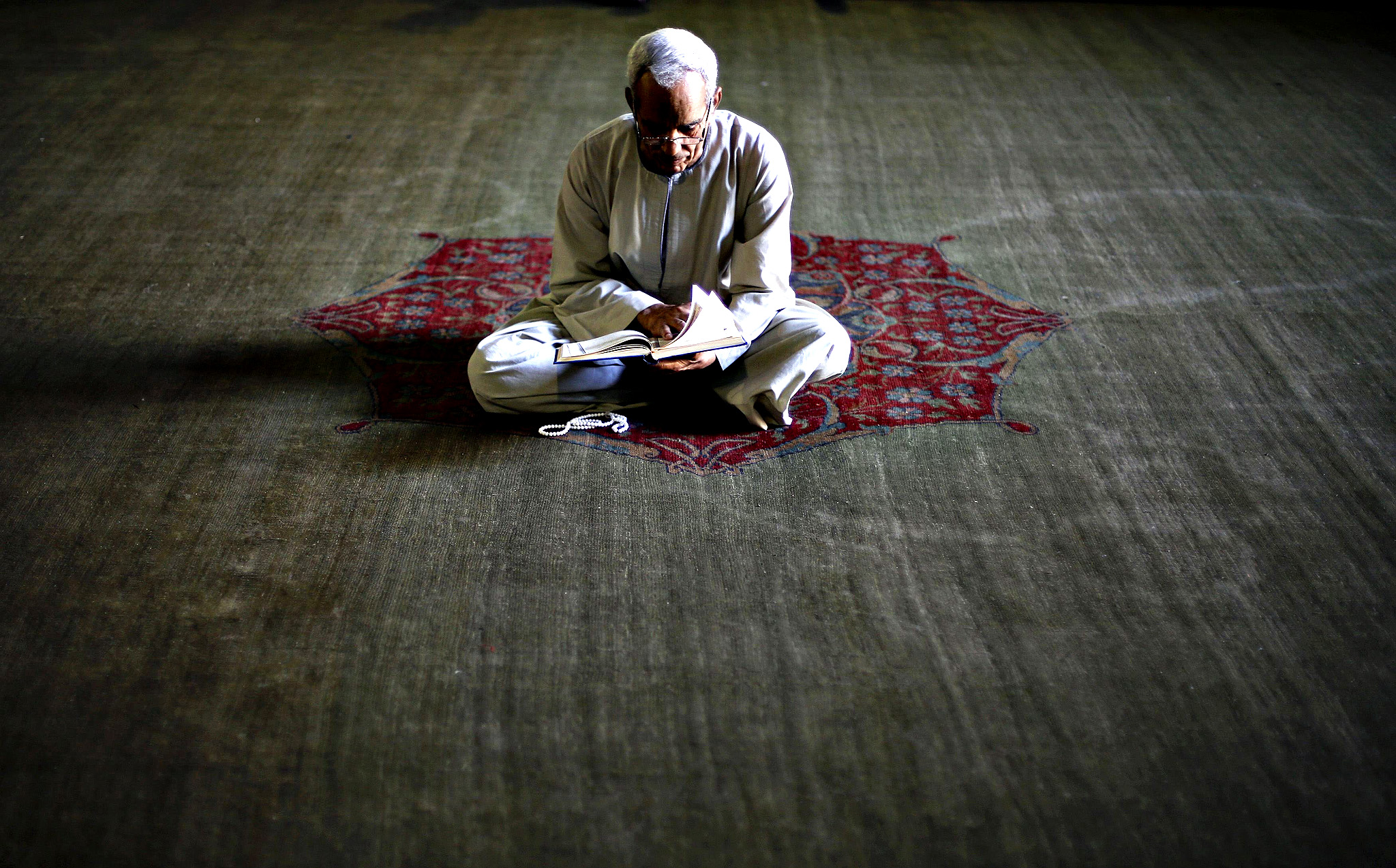 A Muslim man reads the Koran during the holy month of Ramadan inside Al-Refaie mosque in the old Islamic area of Cairo July 16, 2014.