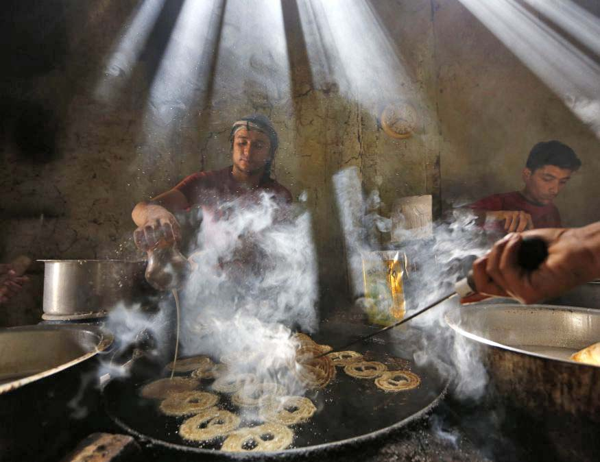 Afghan men make special sweets at a traditional factory in preparation for Eid al-Fitr in Kabul...Afghan men make special sweets at a traditional factory during the holy Muslim fasting month of Ramadan in preparation for Eid al-Fitr in Kabul July 24, 2014. REUTERS/Mohammad Ismail (AFGHANISTAN - Tags: RELIGION FOOD TPX IMAGES OF THE DAY)