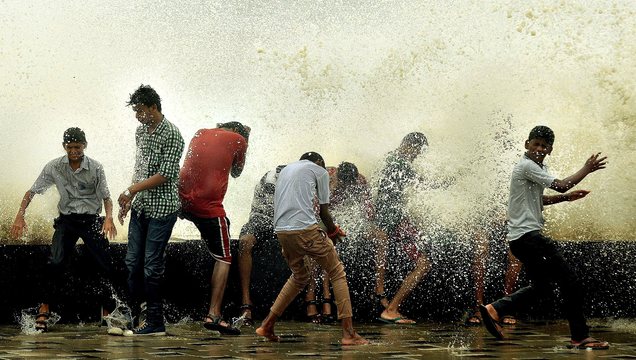 Indians enjoy getting splashed by breaking waves during high tide at the sea front in Mumbai on July 14, 2014. The monsoon rains, which usually hit India from June to September, are crucial for farmers whose crops feed hundreds of millions of people.