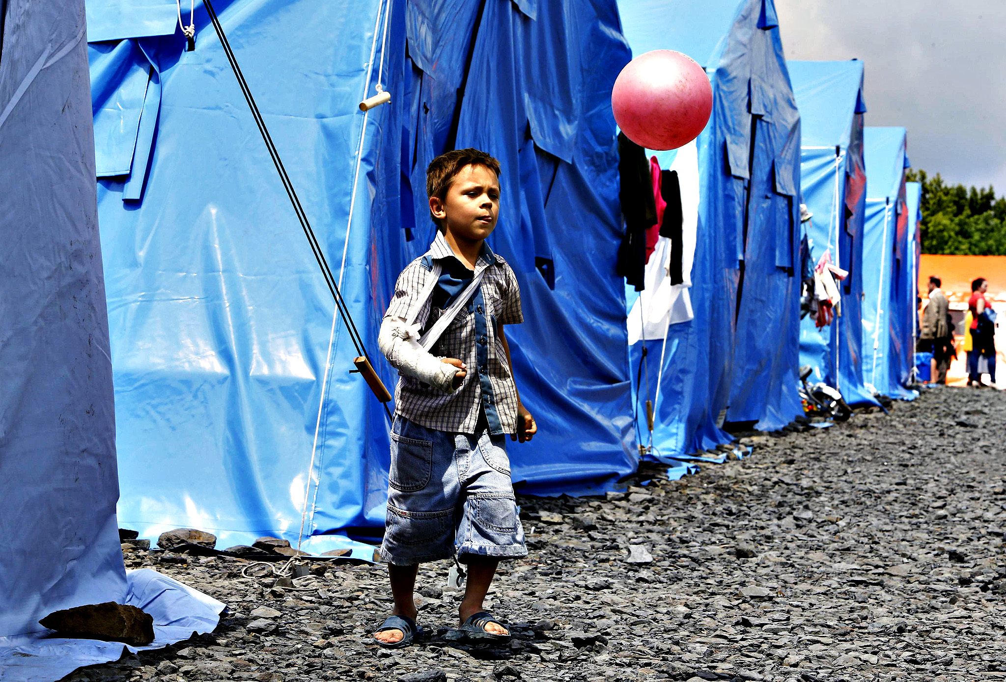 A boy plays with a ball at a temporary tent camp set up for Ukrainian refugees in the town of Novoshakhtinsk in Rostov region near the Russian-Ukrainian border, southern Russia, July 9, 2014.