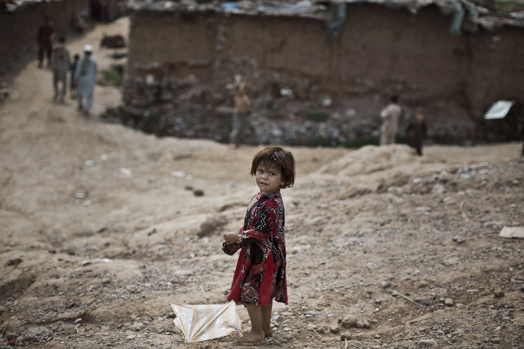 An Afghan refugee child, plays with a kite on the outskirts of Islamabad, Pakistan, Monday, Aug. 11, 2014. (AP Photo/Muhammed Muheisen)