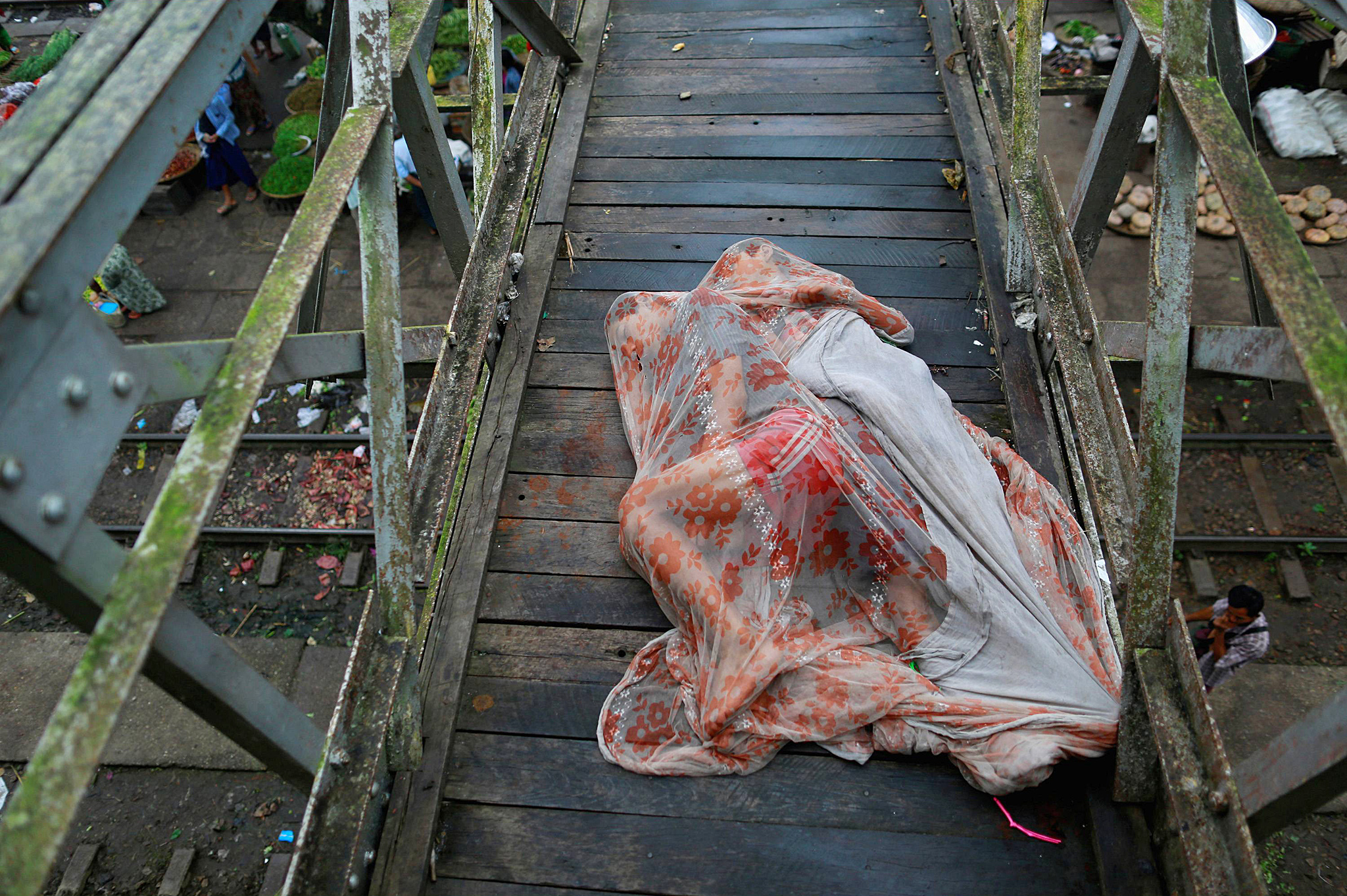 Men sleep covered with a mosquito net on a bridge above a train station outside Yangon August 20, 2014. REUTERS/Soe Z