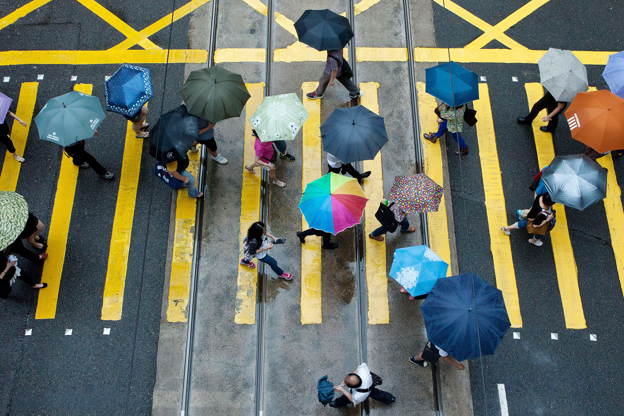 "Pedestrians use umbrellas as they walk in the district of Central in Hong Kong on August 20, 2014. Hong Kong was handed back to China by Britain on July 1, 1997 under a ""one country, two systems"" agreement, which allows residents civil liberties not seen on the mainland, including free speech and the right to protest. But public discontent is at its highest for years notably over Beijing's insistence that it vet candidates before the vote for the city's next leader in 2017."