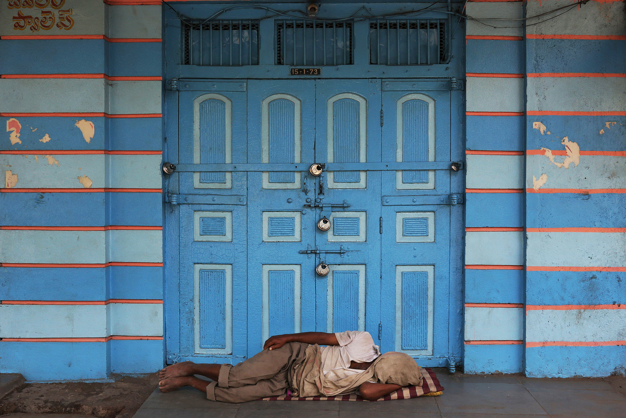 A man sleeps in front of a closed shop in Hyderabad, India, Tuesday, Aug.19, 2014. The city and most parts of the newly created state of Telangana remained shut down Tuesday in view of a household survey undertaken by the new government. (AP Photo/Mahesh Kumar A.)