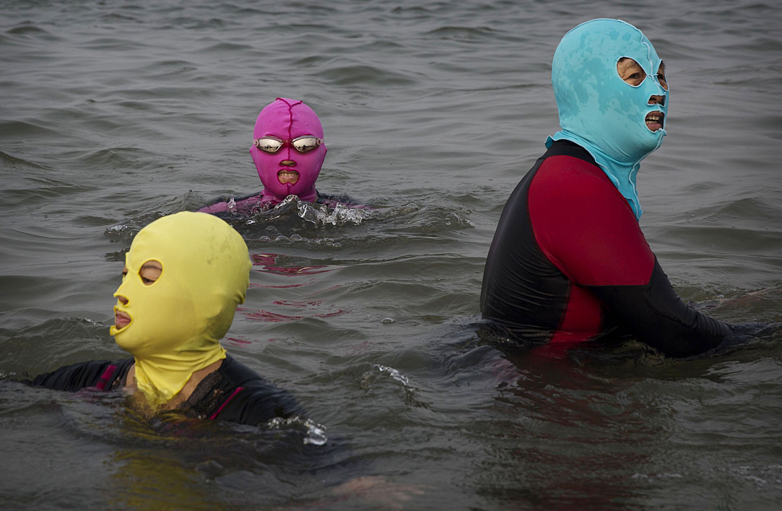 China's Face-kini Becomes Unlikely Global Fashion Hit...QINGDAO, CHINA - AUGUST 21:  A Chinese girl wears a face-kini as she floats in the water on August 21, 2014 on the Yellow Sea in Qingdao, China. The locally designed mask is worn by many local women to protect them from jellyfish stings, algae and the sun's ultraviolet rays.  (Photo by Kevin Frayer/Getty Images)