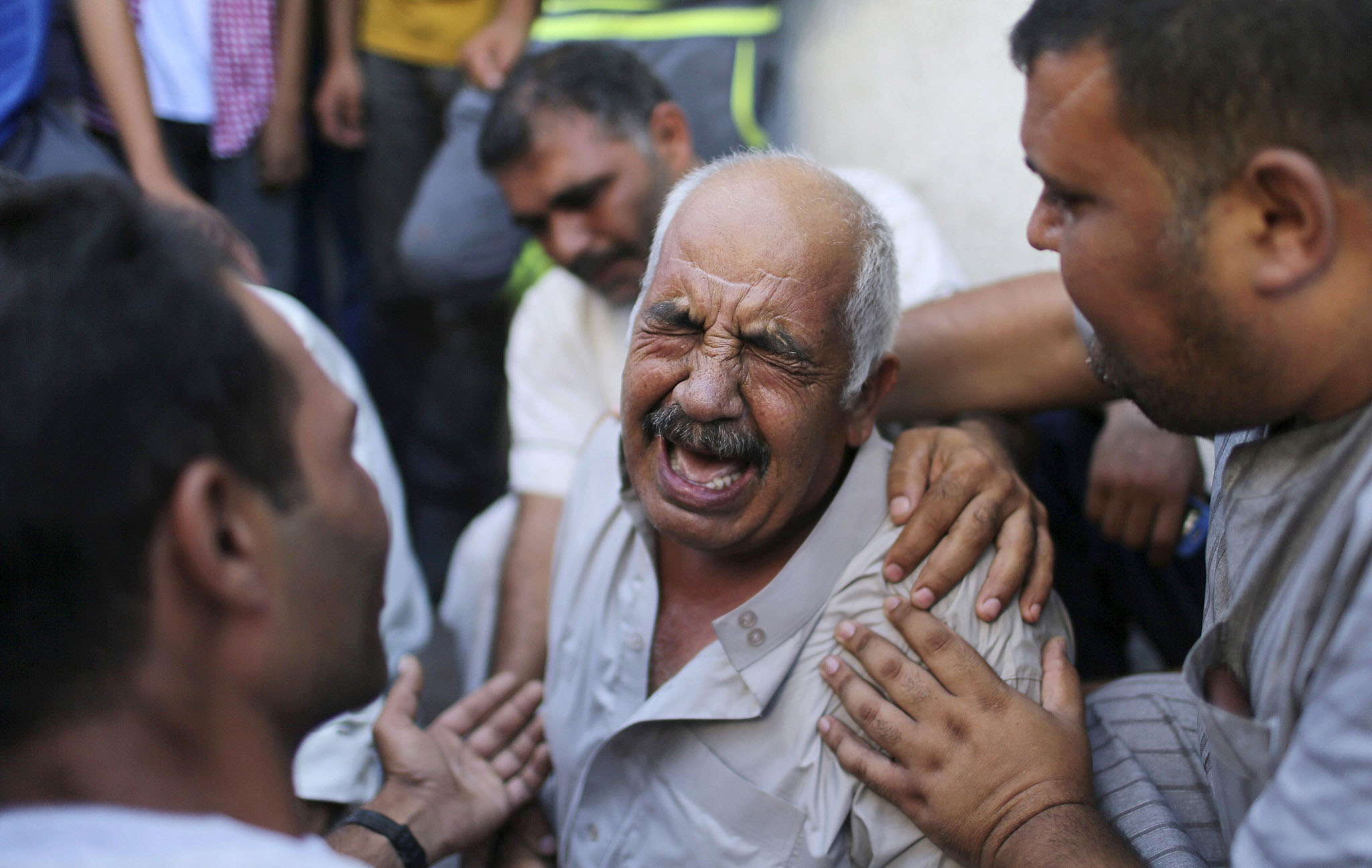 A grandfather of three Palestinian children cries outside a hospital morgue in Gaza City...REFILE - CORRECTING YEAR  A grandfather of three Palestinian children who medics said were killed in an Israeli air strike, cries outside a hospital morgue in Gaza City August 21, 2014. An Israeli air strike killed three senior Hamas military commanders in the Gaza Strip on Thursday, the Islamist group said, the clearest sign yet Israel is focusing its assault on those leading attacks from the Palestinian enclave. The Israeli military had no immediate comment on what would constitute the killing of the most senior Hamas men since it launched its offensive on Gaza six week ago with the declared aim of curbing rocket fire into its territory. REUTERS/Suhaib Salem (GAZA - Tags: CIVIL UNREST POLITICS TPX IMAGES OF THE DAY CONFLICT)