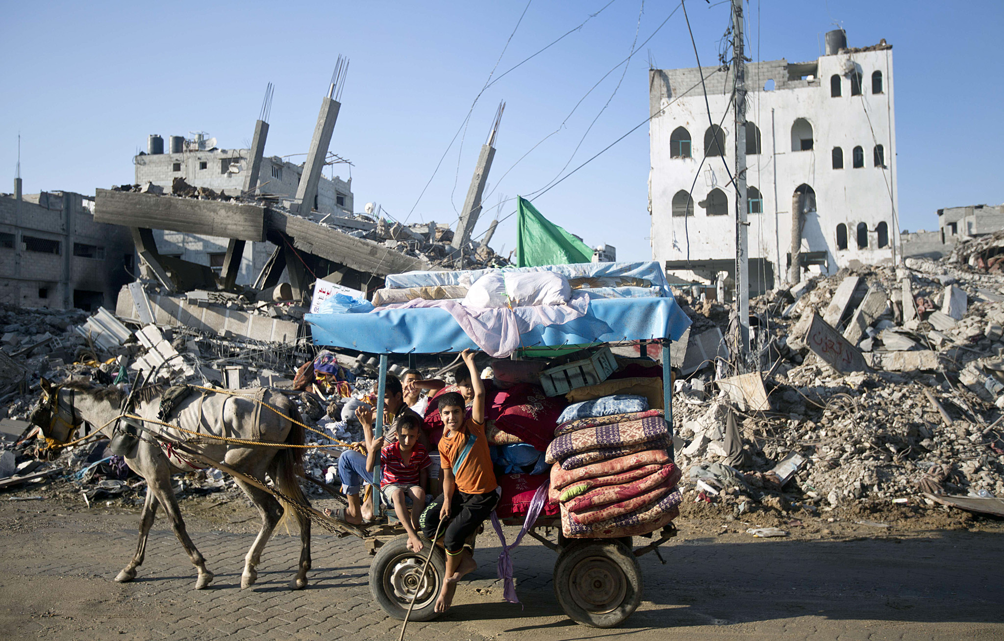 A group of Palestinian boys ride horse-d...A group of Palestinian boys ride horse-drawn cart past destroyed houses in the Shejaiya neighborhood of Gaza City on August 27, 2014, following the long-term truce agreed between Israel and the Palestinians. After seven weeks of the deadliest Israeli-Palestinian violence in a decade, a long-term ceasefire took hold at 1600 GMT on August 26, sparking festivities around the Gaza Strip. AFP PHOTO/MAHMUD HAMSMAHMUD HAMS/AFP/Getty Images