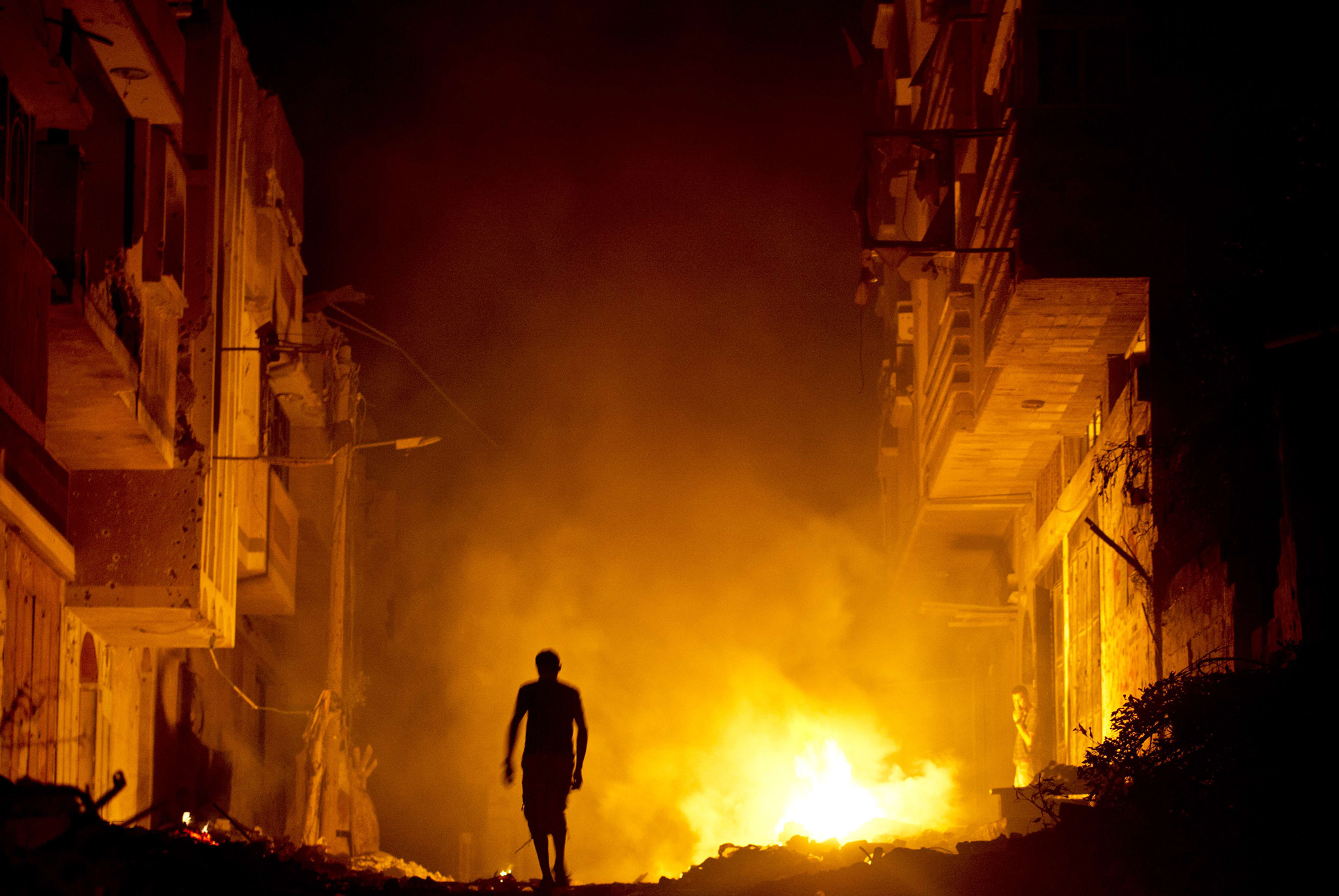 A Palestinian man walks past a fire in a street set by a home owner in an effort to keep mosquitoes away from their shattered homes in Shejaiya on August 27, 2014. Shejaiya was one of the hardest hit neighborhoods in fighting between Hamas militants and Israel during 50 days of fighting. Israel and Palestinians both boasted of victory in the Gaza war but analysts say Hamas received only promises while the conflict aggravated divisions in the Israeli leadership.  AFP PHOTO/ROBERTO SCHMIDTROBERTO SCHMIDT/AFP/Getty Images
