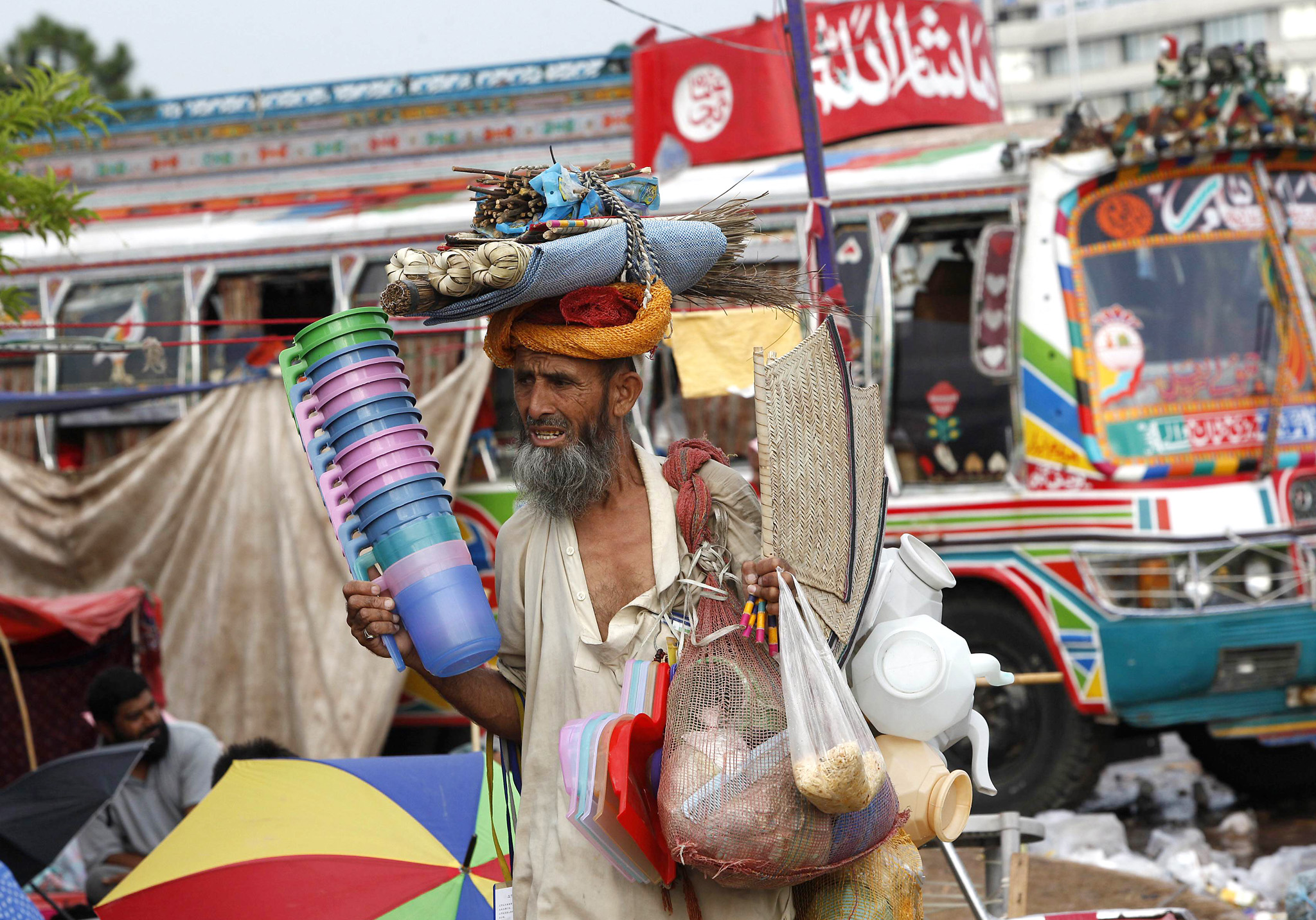 "A man peddles household goods to supporters of Qadri, during the Revolution March in Islamabad...A man peddles household goods to supporters (unseen) of populist cleric Tahir ul-Qadri, leader of political party Pakistan Awami Tehreek (PAT), in front of the Parliament house building during the Revolution March in Islamabad August 27, 2014. Thousands of protesters, led by opposition leader Imran Khan and Qadri, are now camped out in the heart of Islamabad - the so-called ""Red Zone"".  REUTERS/Akhtar Soomro (PAKISTAN - Tags: POLITICS CIVIL UNREST)"
