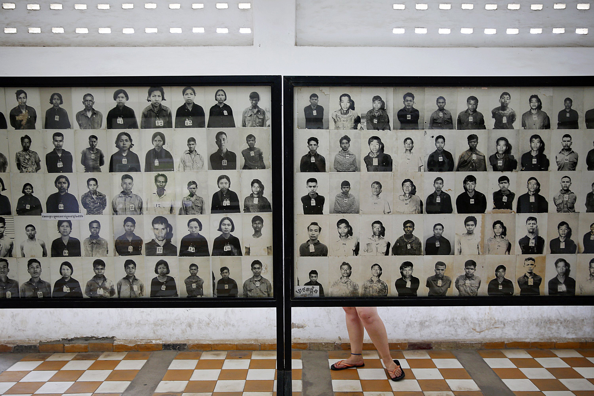 A visitor looks at pictures of victims of Khmer Rouge regime at the former notorious Tuol Sleng prison that is now the Genocide Museum, in Phnom Penh...A visitor looks at pictures of victims of Khmer Rouge regime at the former notorious Tuol Sleng prison that is now the Genocide Museum, in Phnom Penh August 5, 2014. Cambodia's young population is very aware of its grim history, with almost every family suffering losses. Most Cambodians still want justice and to see the U.N.-backed court find the recalcitrant Nuon Chea, Pol Pot's right-hand man, and ex-President Khieu Samphan, guilty of crimes against humanity, but the court has been mired in disputes, resignations, funding shortages and accusations of political interference and has to date delivered just one verdict. The court will deliver verdicts for Noun Chea and Khieu Samphan on August 7, 2014. Picture taken August 5, 2014. REUTERS/Damir Sagolj(CAMBODIA - Tags: POLITICS CIVIL UNREST CRIME LAW)