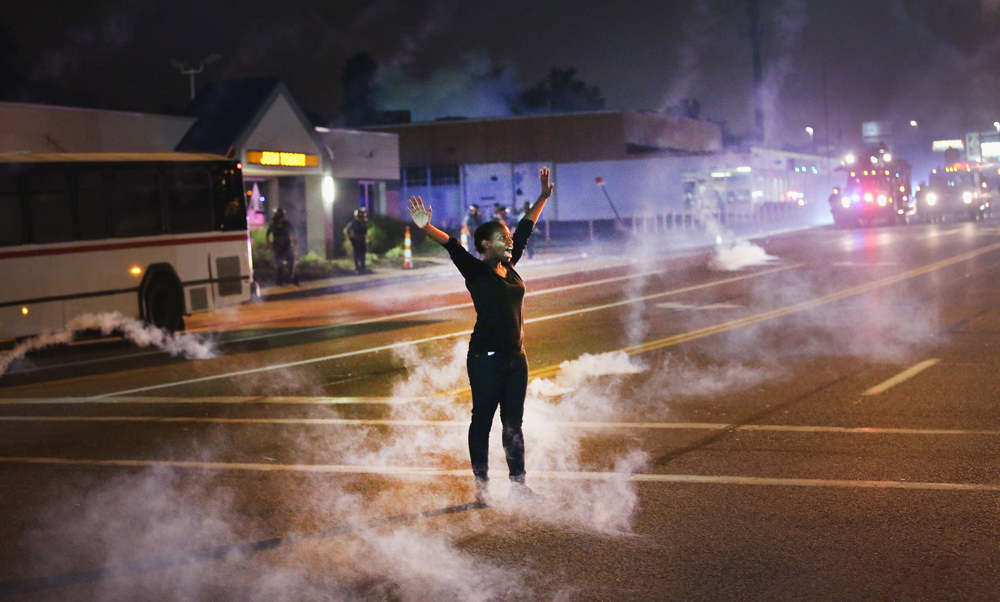 Outrage In Missouri Town After Police Shooting Of 18-Yr-Old Man...FERGUSON, MO - AUGUST 17:  Tear gas reigns down on a woman standing with her arms raised in the street after a demonstration over the killing of teenager Michael Brown by a Ferguson police on August 17, 2014 in Ferguson, Missouri. Despite the Brown family's continued call for peaceful demonstrations, violent protests have erupted nearly every night in Ferguson since his August 9, death.  (Photo by Scott Olson/Getty Images)