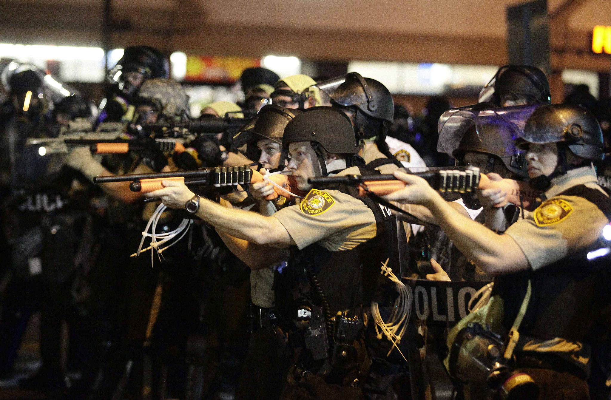 Police officers point their weapons at demonstrators protesting against the shooting death of Michael Brown in Ferguson, Missouri...Police officers point their weapons at demonstrators protesting against the shooting death of Michael Brown in Ferguson, Missouri August 18, 2014. Police fired tear gas and stun grenades at protesters on Monday after days of unrest sparked by the fatal shooting of unarmed black teenager Michael Brown by a white policeman. REUTERS/Joshua Lott (UNITED STATES - Tags: CRIME LAW CIVIL UNREST)