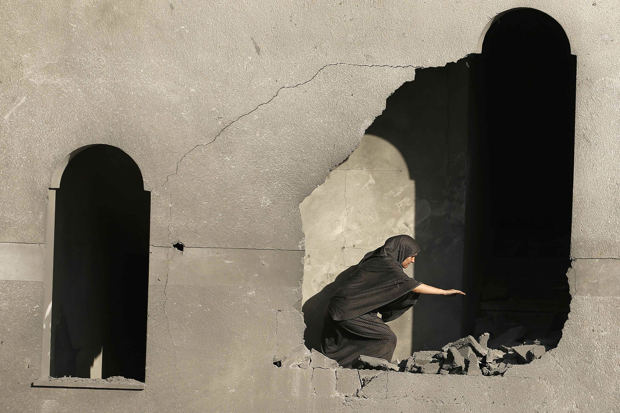 A Palestinian woman inspects her house that witnesses said was damaged during an Israeli airstrike in Gaza City
