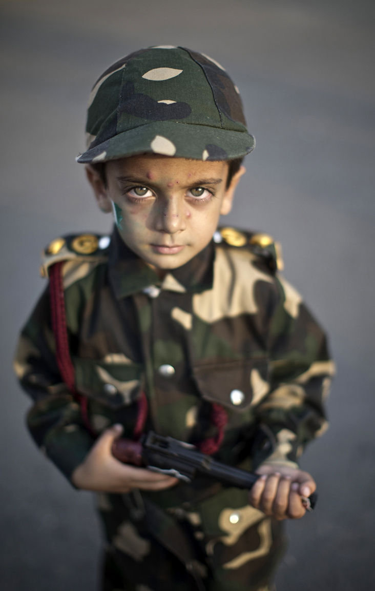 Pakistani child, Harris Khan, 4, wearing a millitary uniform and holding a toy gun, poses for a picture while he and other Pakistanis celebrate the 68th Independence Day, in Islamabad, Pakistan, Thursday, Aug. 14, 2014. (AP Photo/Muhammed Muheisen)