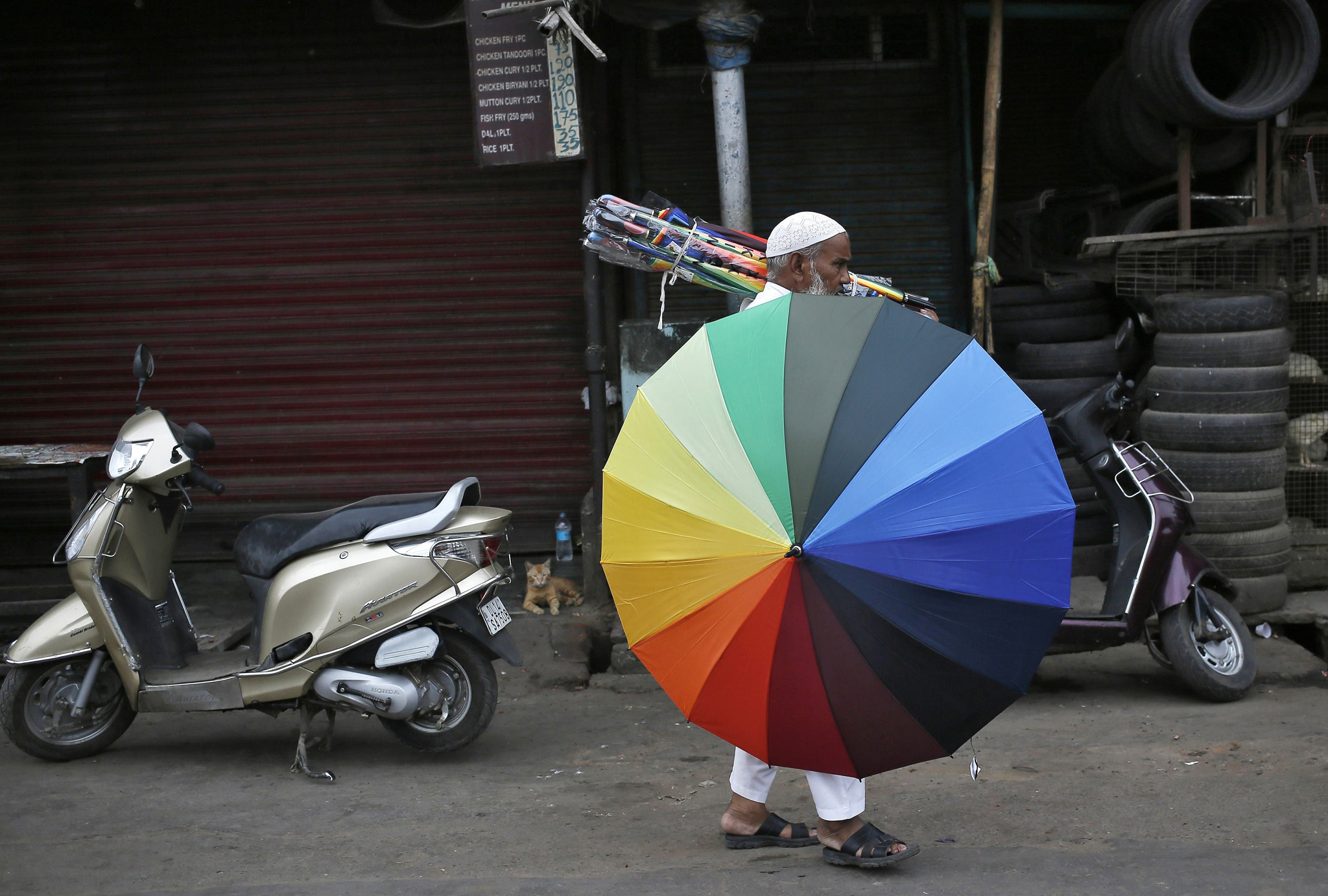An umbrella seller walks along a road in the old quarters of Del