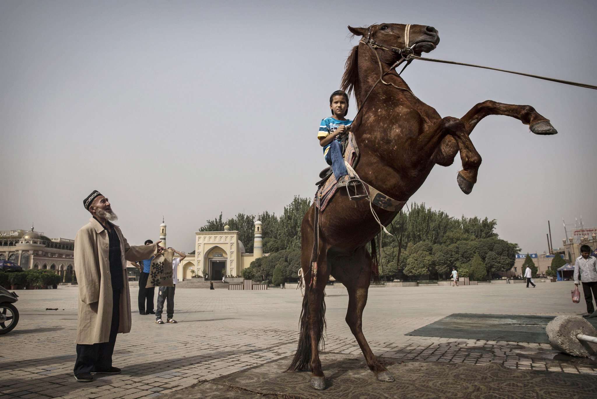 Uyghur Life Persists in Kashgar Amid Growing Tension in Restive Xinjiang Province...KASHGAR, CHINA - JULY 28:  A Uyghur boy sits atop a horse as he has his picture taken outside the Id Kah Mosque before the Eid holiday  on July 28, 2014 in old Kashgar, Xinjiang Province, China. Nearly 100 people have been killed in unrest in the restive Xinjiang Province in the last week in what authorities say is terrorism but advocacy groups claim is a result of a government crackdown to silence opposition to its policies. China's Muslim Uyghur ethnic group faces cultural and religious restrictions by the Chinese government. Beijing says it is investing heavily in the Xinjiang region but Uyghurs are increasingly dissatisfied with the influx of Han Chinese and uneven economic development.  (Photo by Kevin Frayer/Getty Images)
